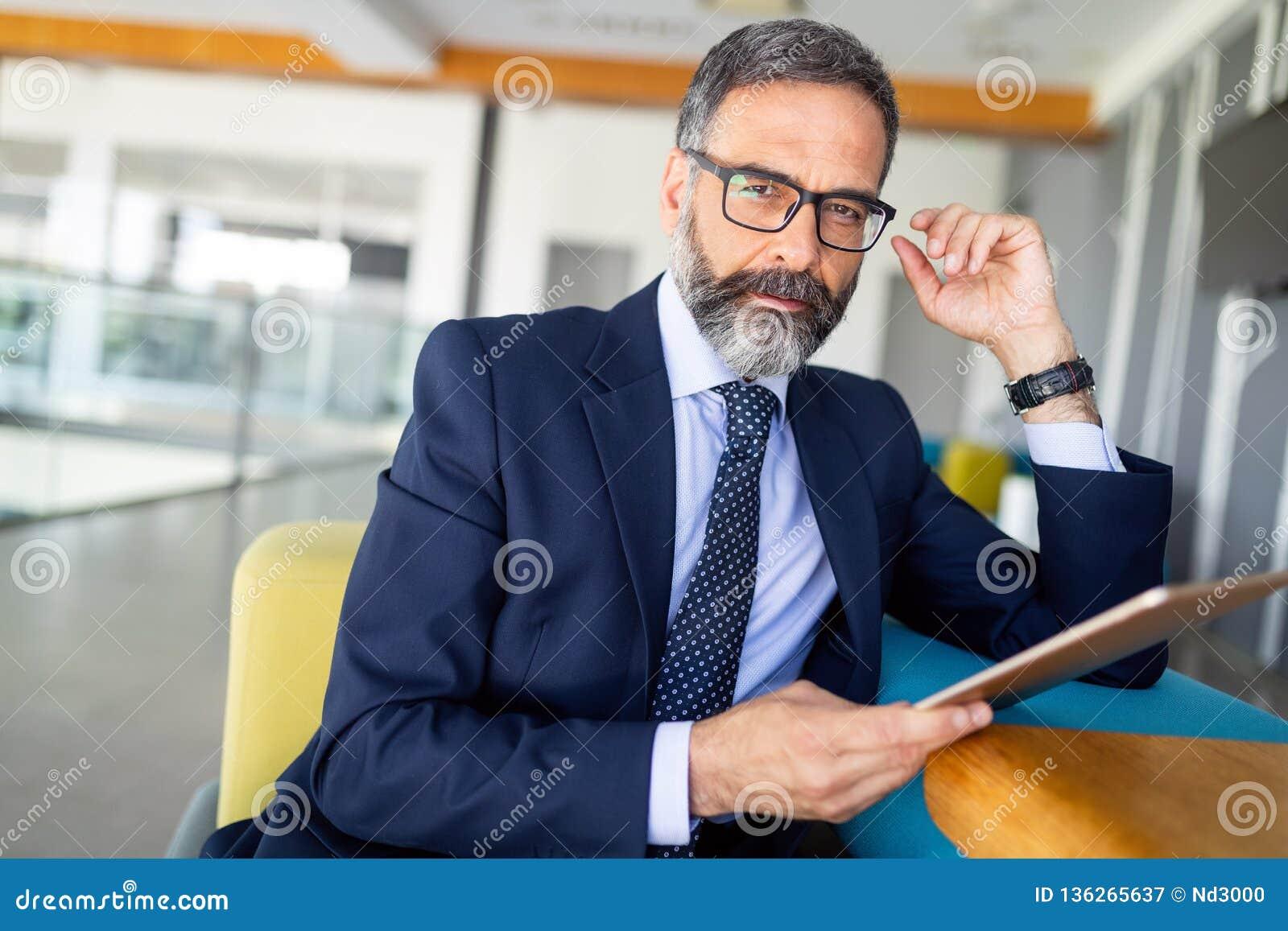 英俊的资深商人画象与数字片剂的在modren办公室