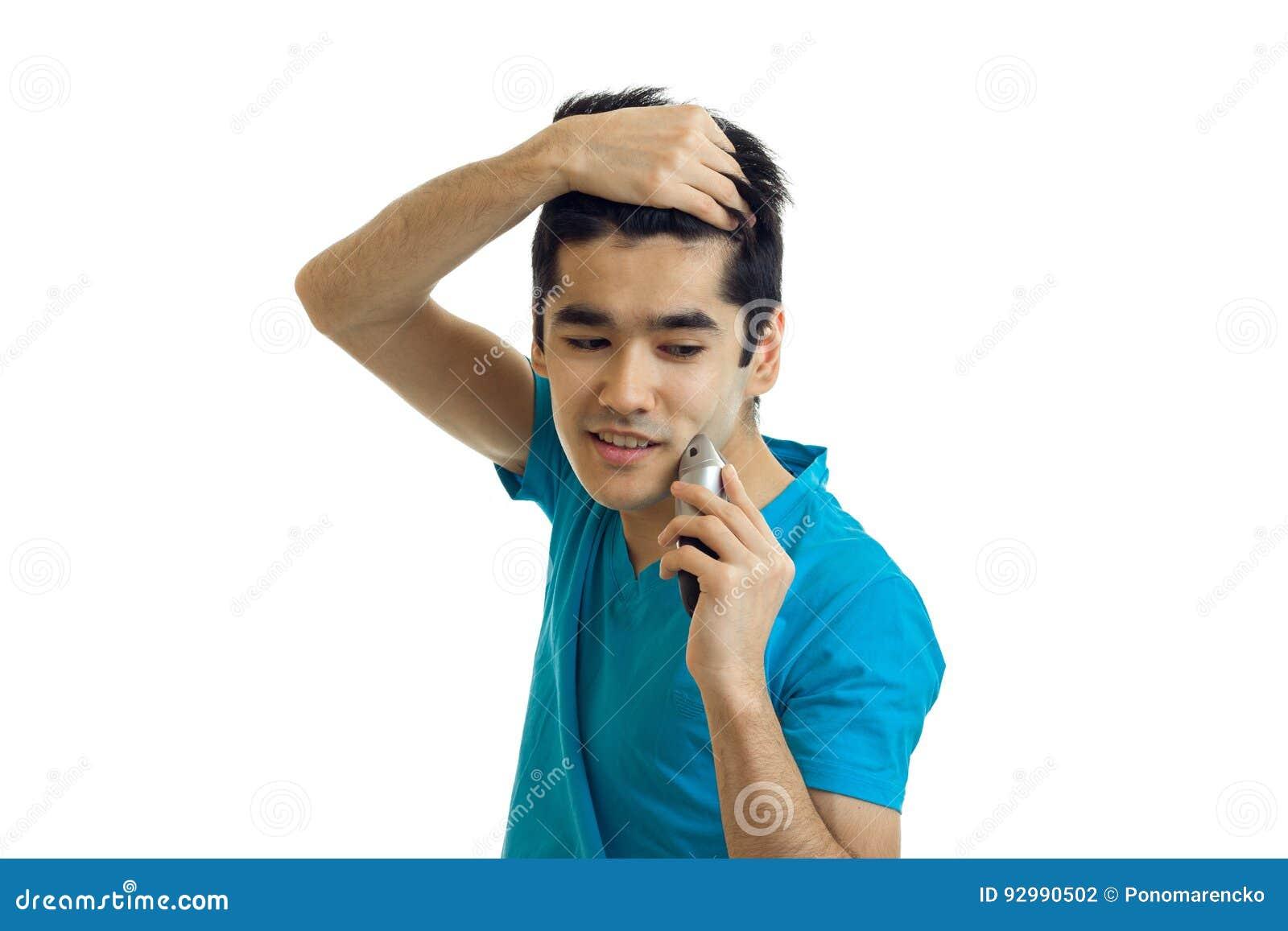 英俊年轻人微笑在白色背景保留手头发神色并且刮他的胡子被隔绝