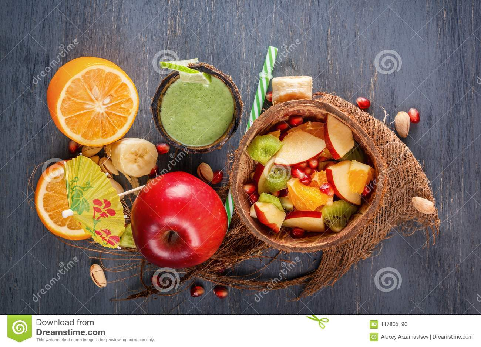 苹果、香蕉、桔子和石榴在一半椰子和新鲜的绿色圆滑的人水果沙拉从菜