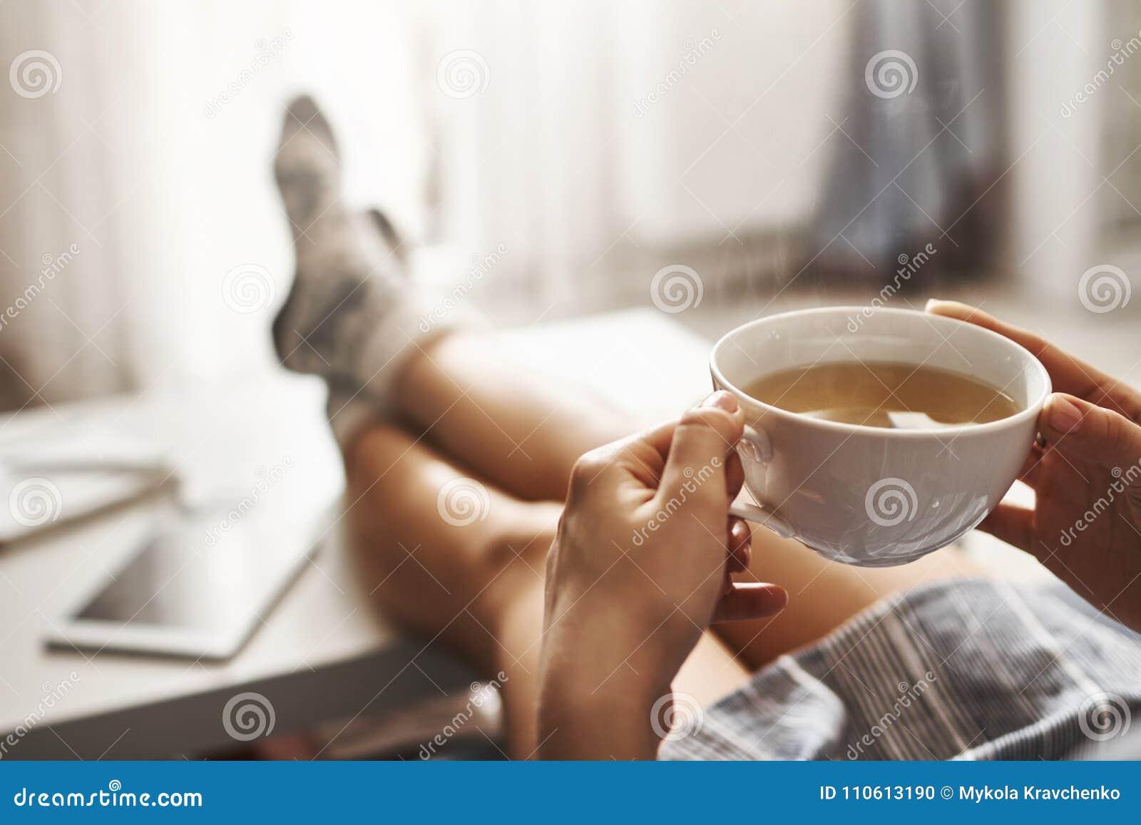 茶和冷颤 说谎在长沙发,握在咖啡桌,饮用的热的咖啡上的腿和享受早晨的妇女