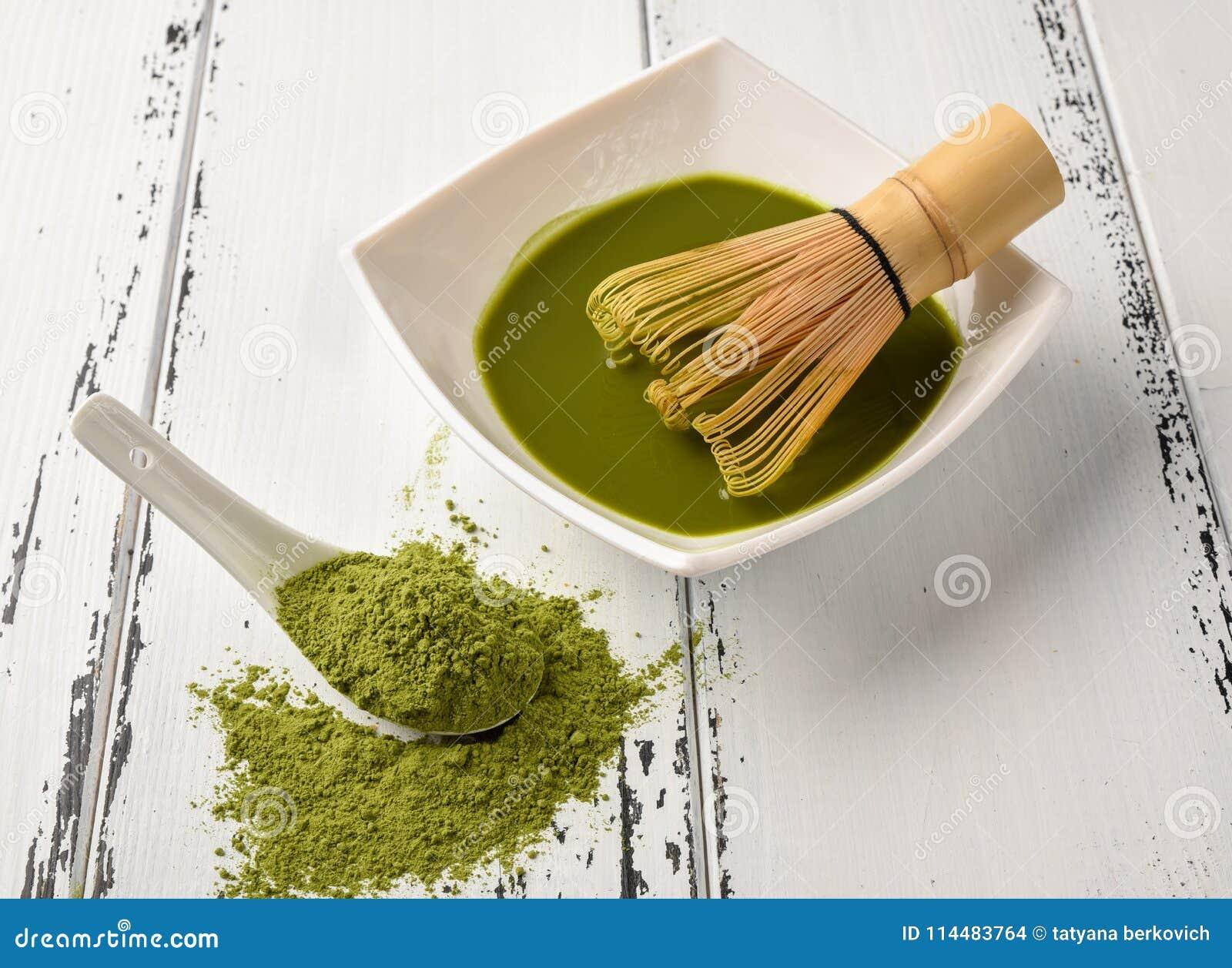 茶比赛的准备:滚保龄球与扫和茶杯,绿茶在一把白色陶瓷匙子的比赛粉末