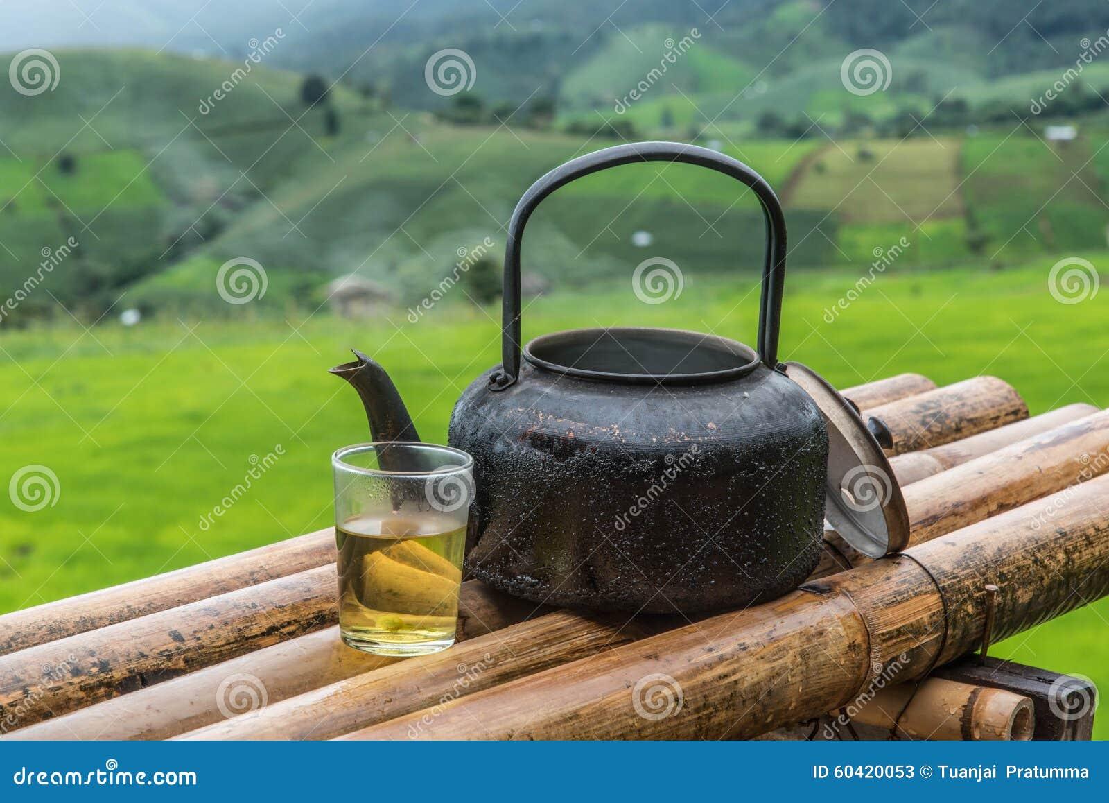 茶煮沸的老铝水壶和一杯茶