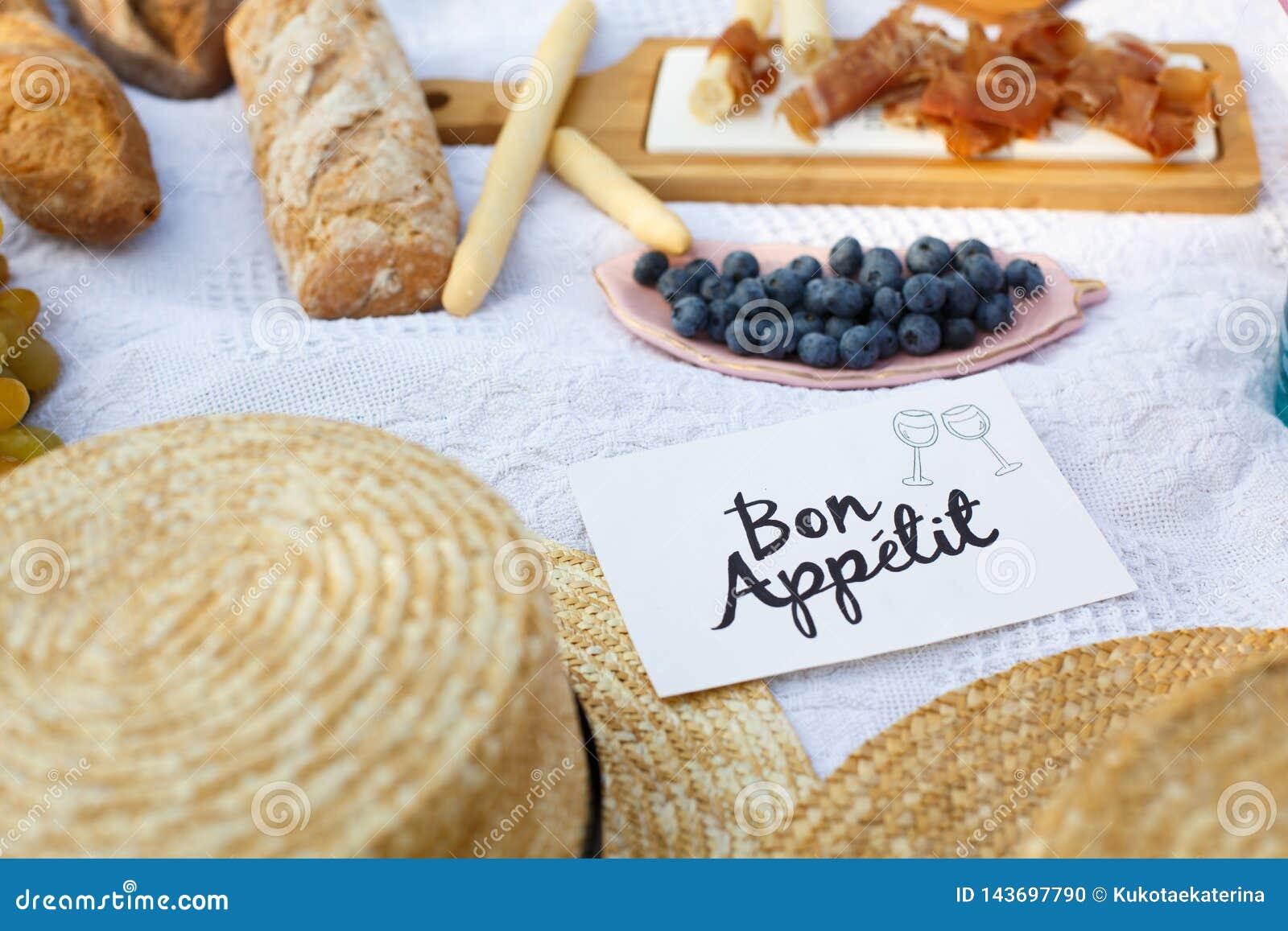 草帽在一条白色野餐毯子放置在标识牌好的妙语apetit明亮的夏日背景旁边 夏天过周末休闲