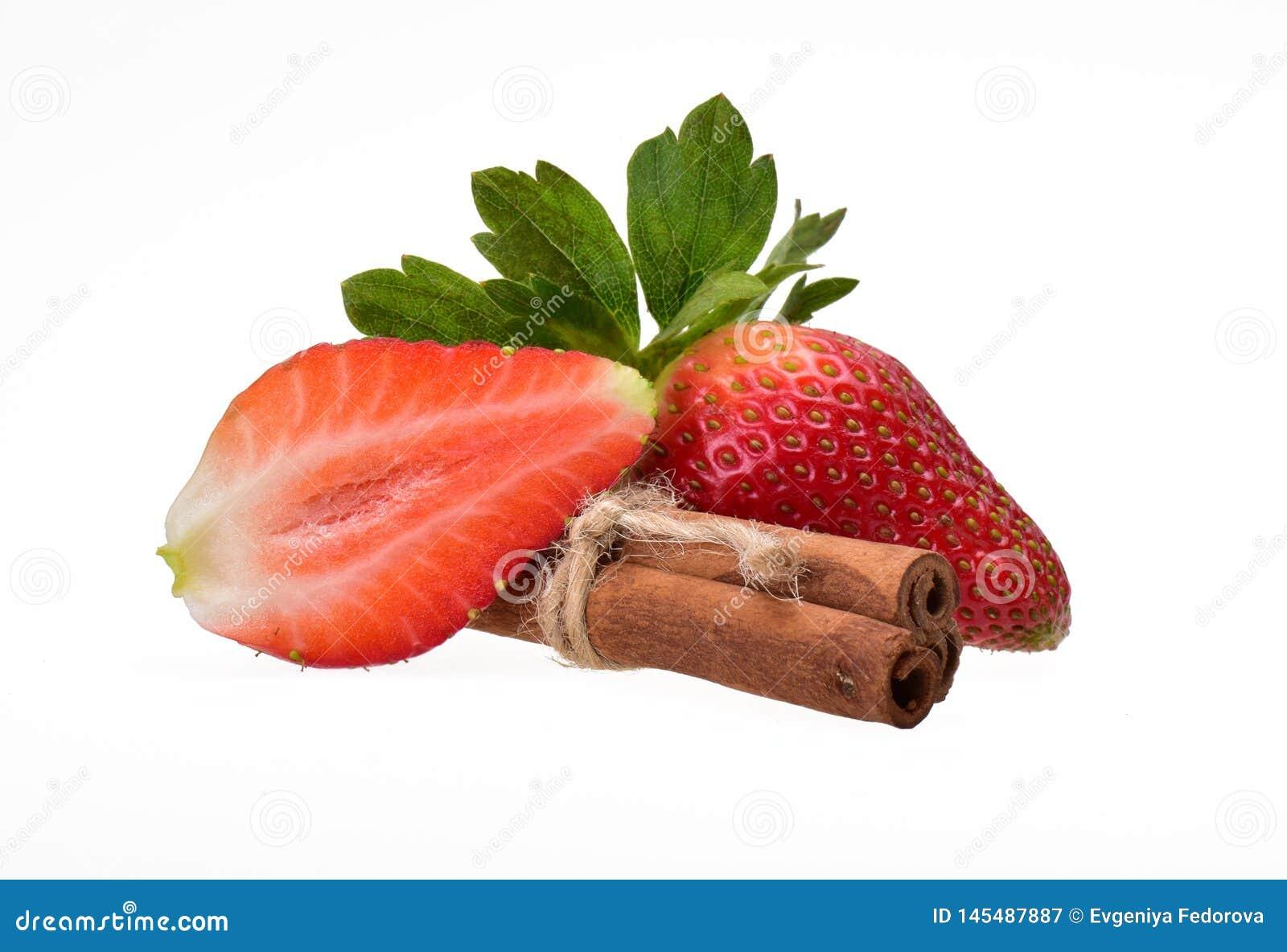 草莓,整个和对分与绿色叶子和三根肉桂条