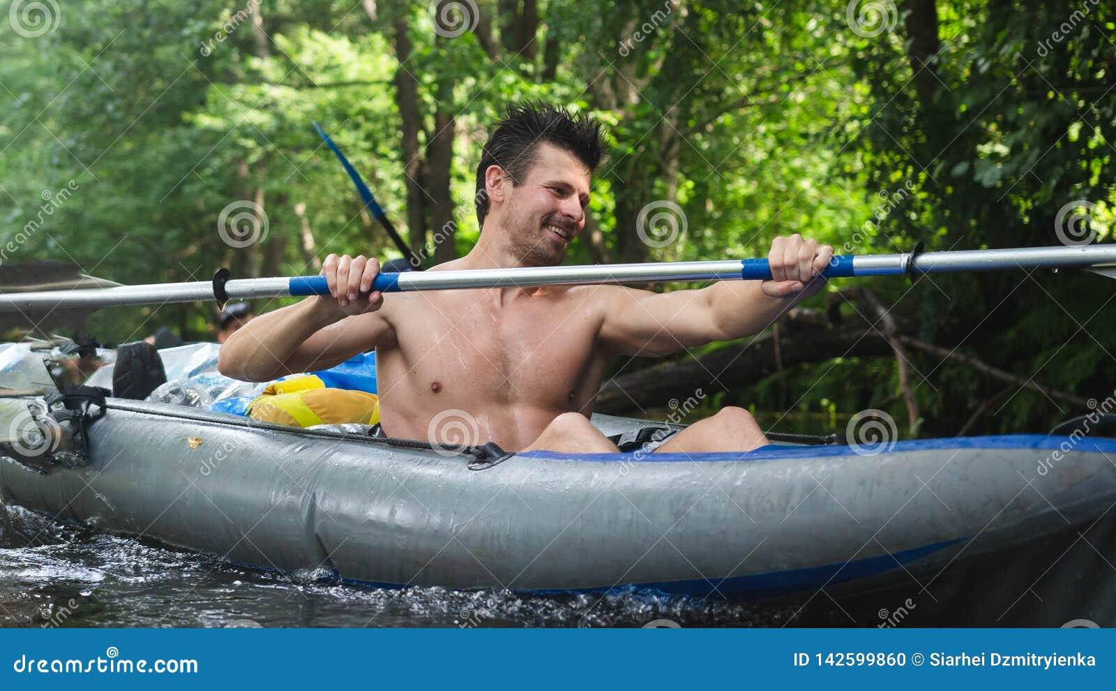 荡桨在河漂流的小船桨的帅哥 划皮船的 独木舟的人用浆划桨的