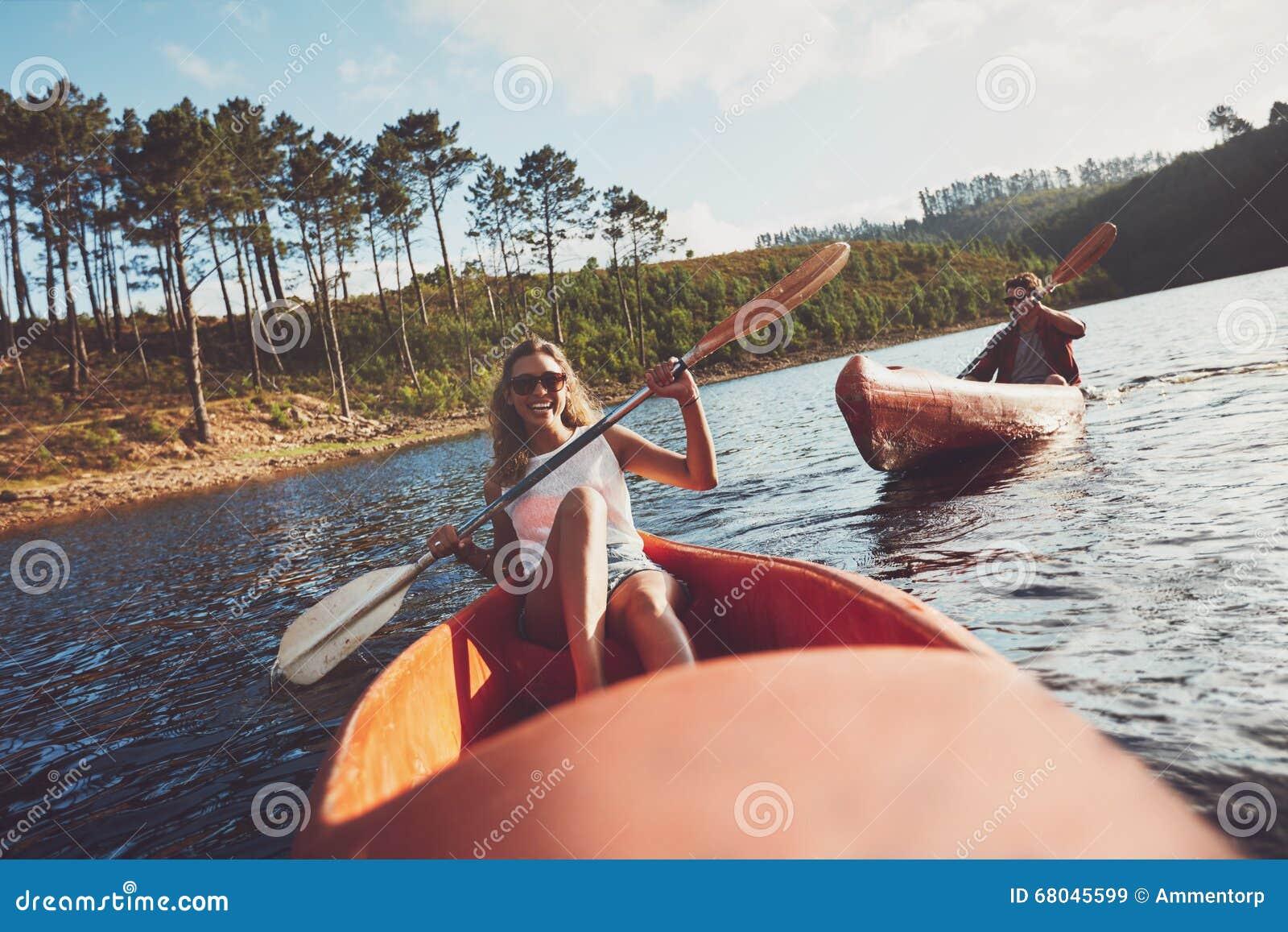 阴荡少妇网_划皮船在湖的青年人 有人的微笑的少妇的皮艇在背景中的用浆划皮船.