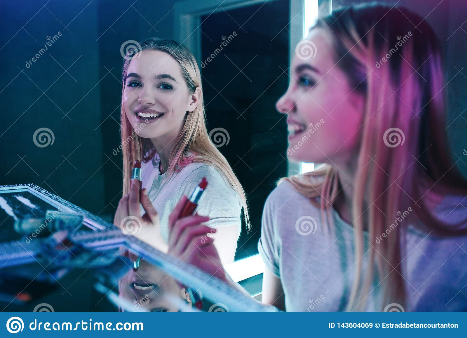药物毁坏您 年轻吸毒者在服在夜总会的洗手间的药以后笑并且绘她的嘴唇 令人上瘾