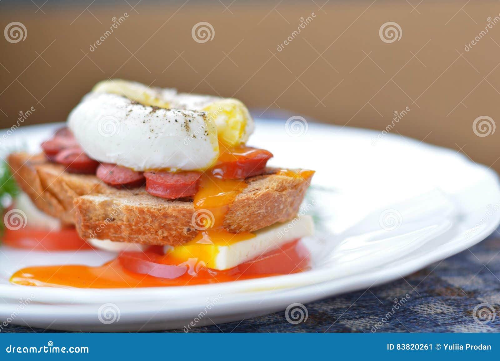 荷包蛋橙色,连续卵黄质在香肠,面包,希脂乳chesse,蕃茄接近的