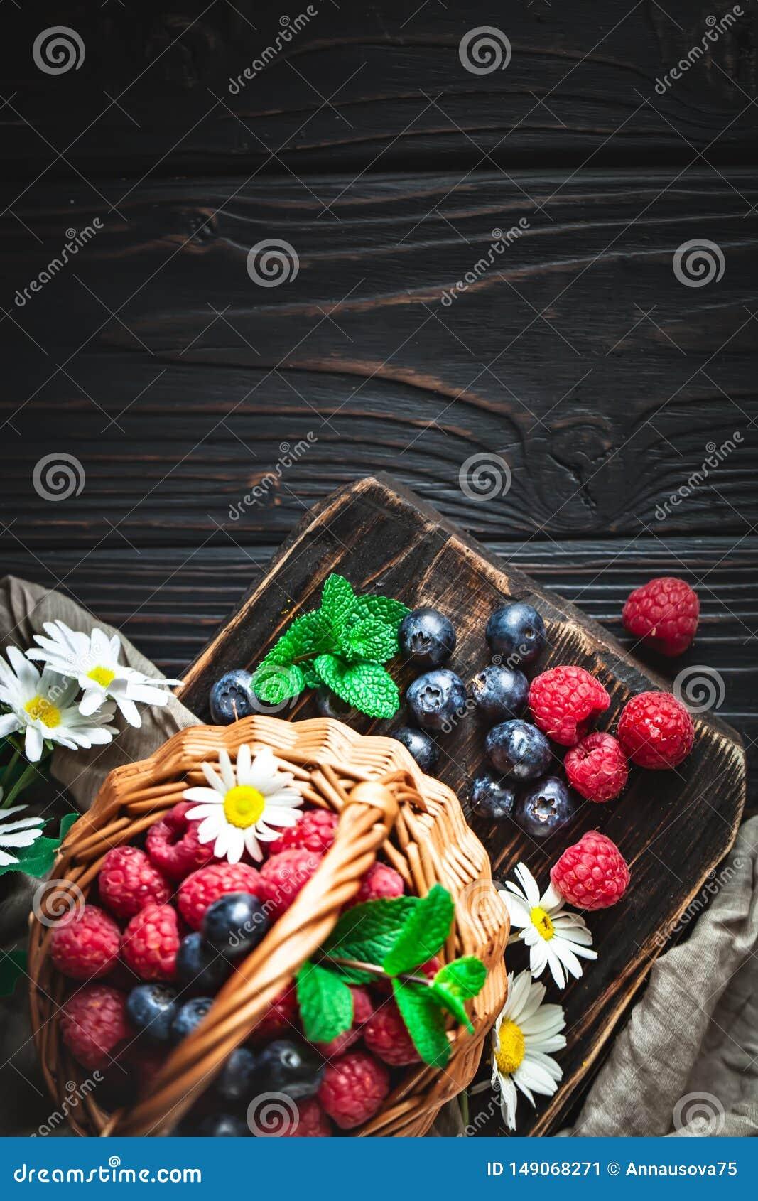 莓和蓝莓在一个篮子与春黄菊和叶子在黑暗的背景 夏天和健康食品概念