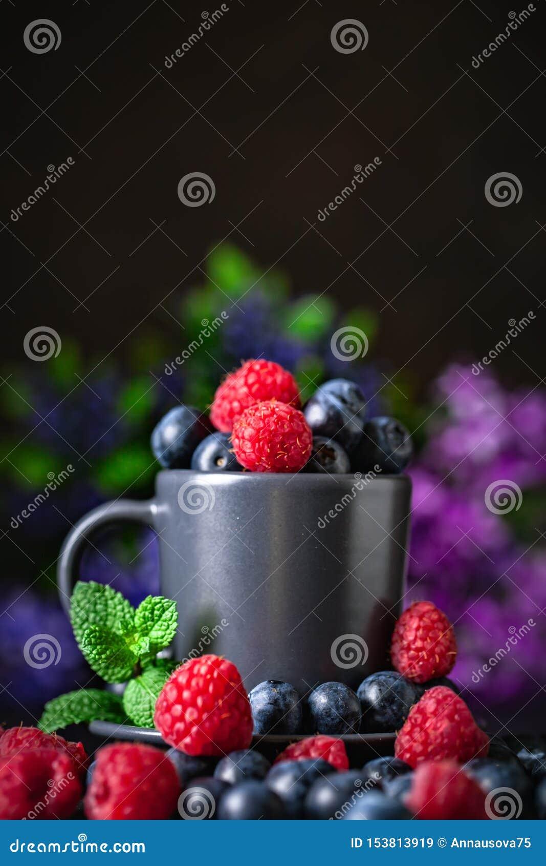 莓和蓝莓在一杯在黑暗的背景 夏天和健康食品概念 r