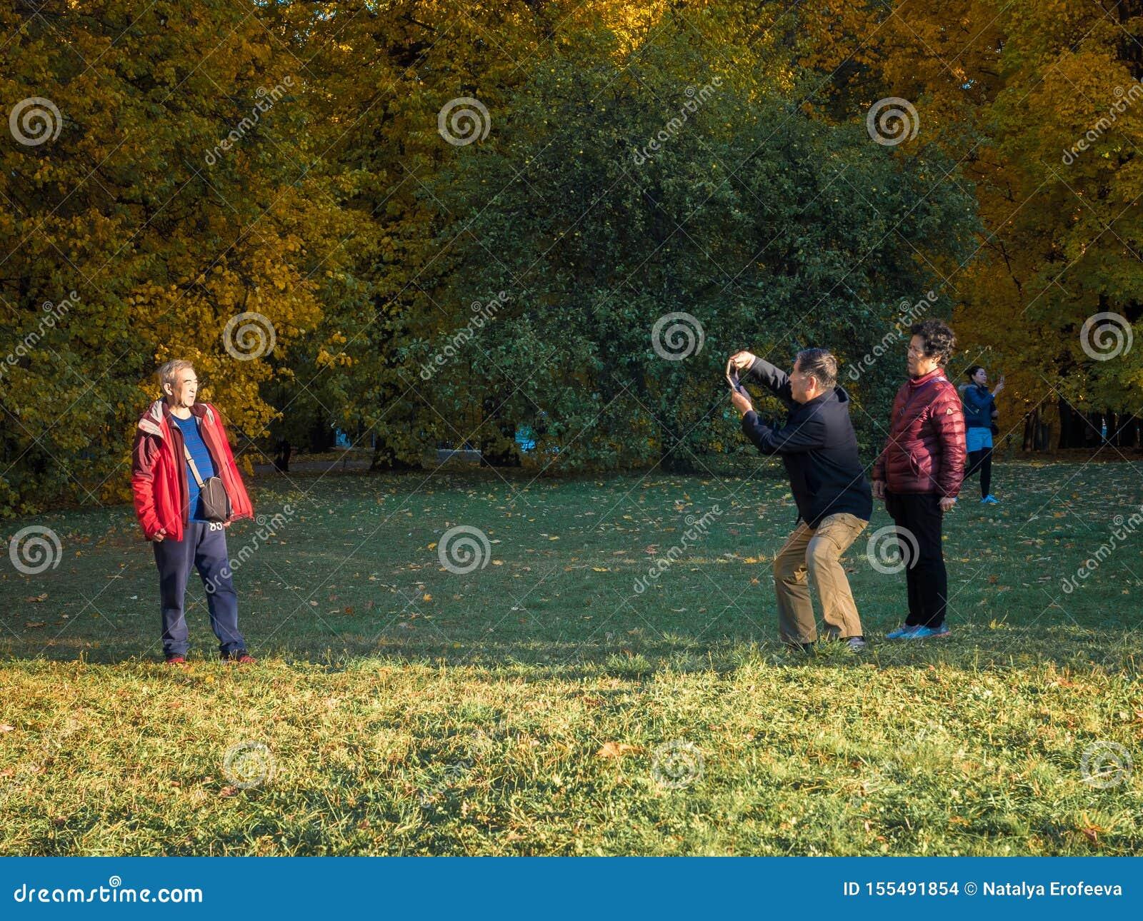 莫斯科,俄罗斯- 2018年10月11日:中国游客走秋天公园 年长亚裔人民拍在的照片