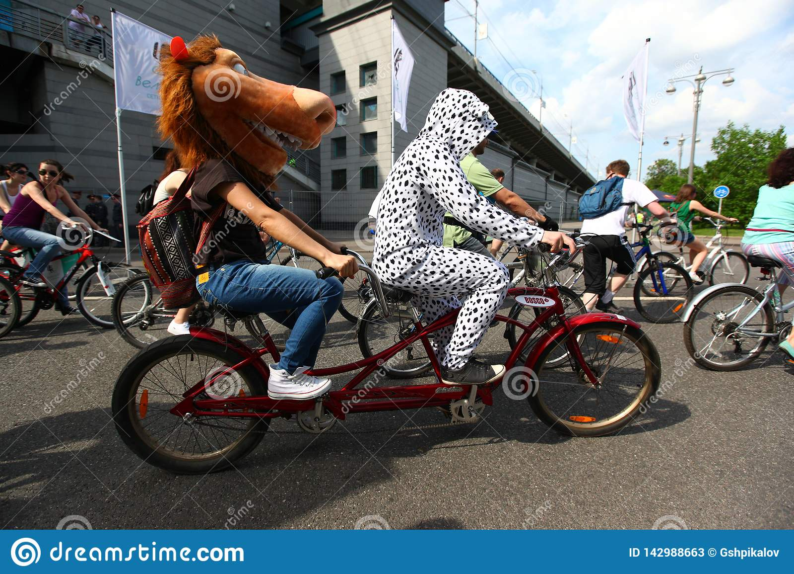 莫斯科,俄罗斯- 2002年5月20日:城市循环的游行、马和dalmation打扮了一辆纵排自行车的参加者