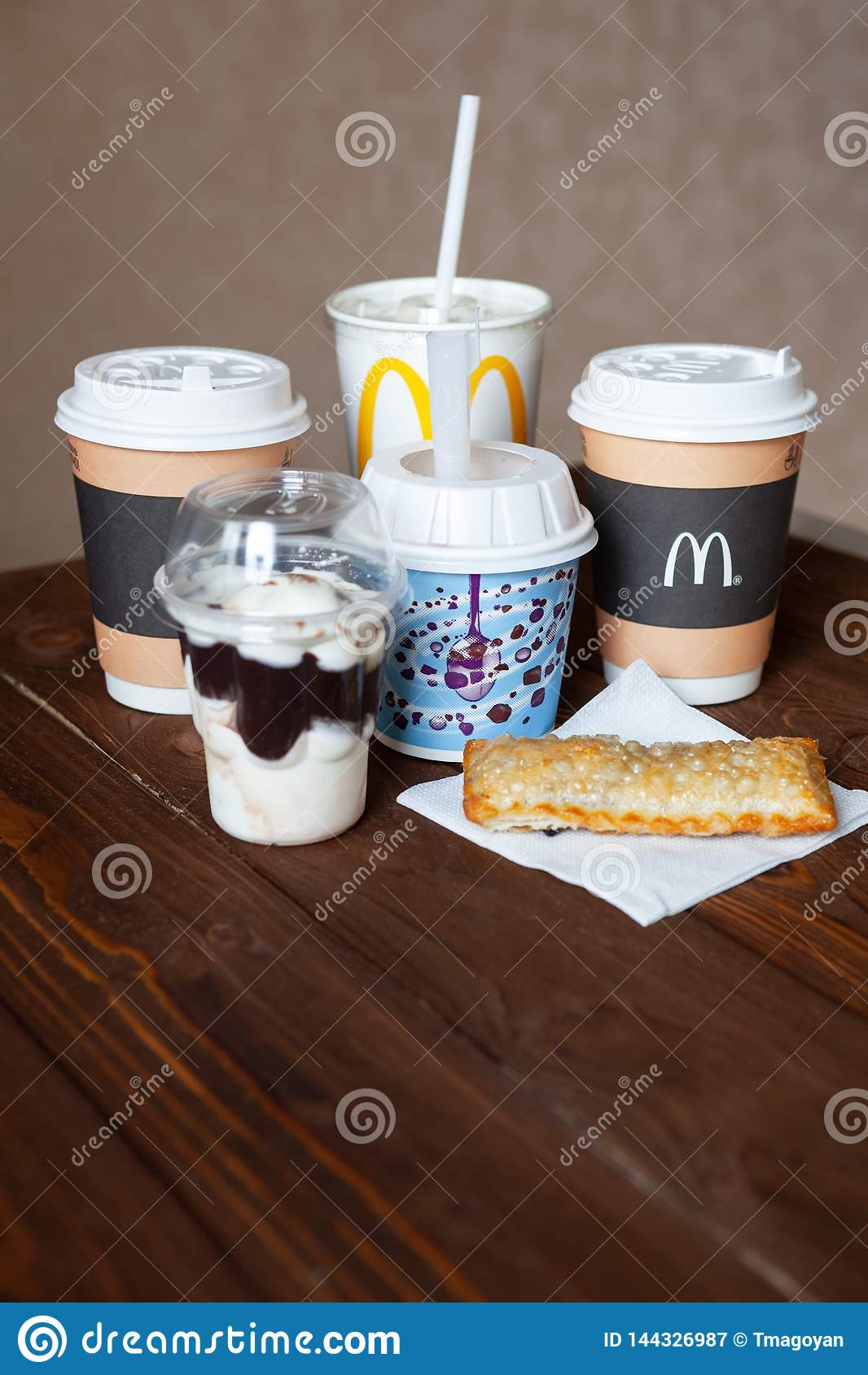 莫斯科,俄罗斯- 2019年4月06日:麦克唐纳食物交付 点心和热的饮料在木桌上 特写镜头 侧视图 垂直