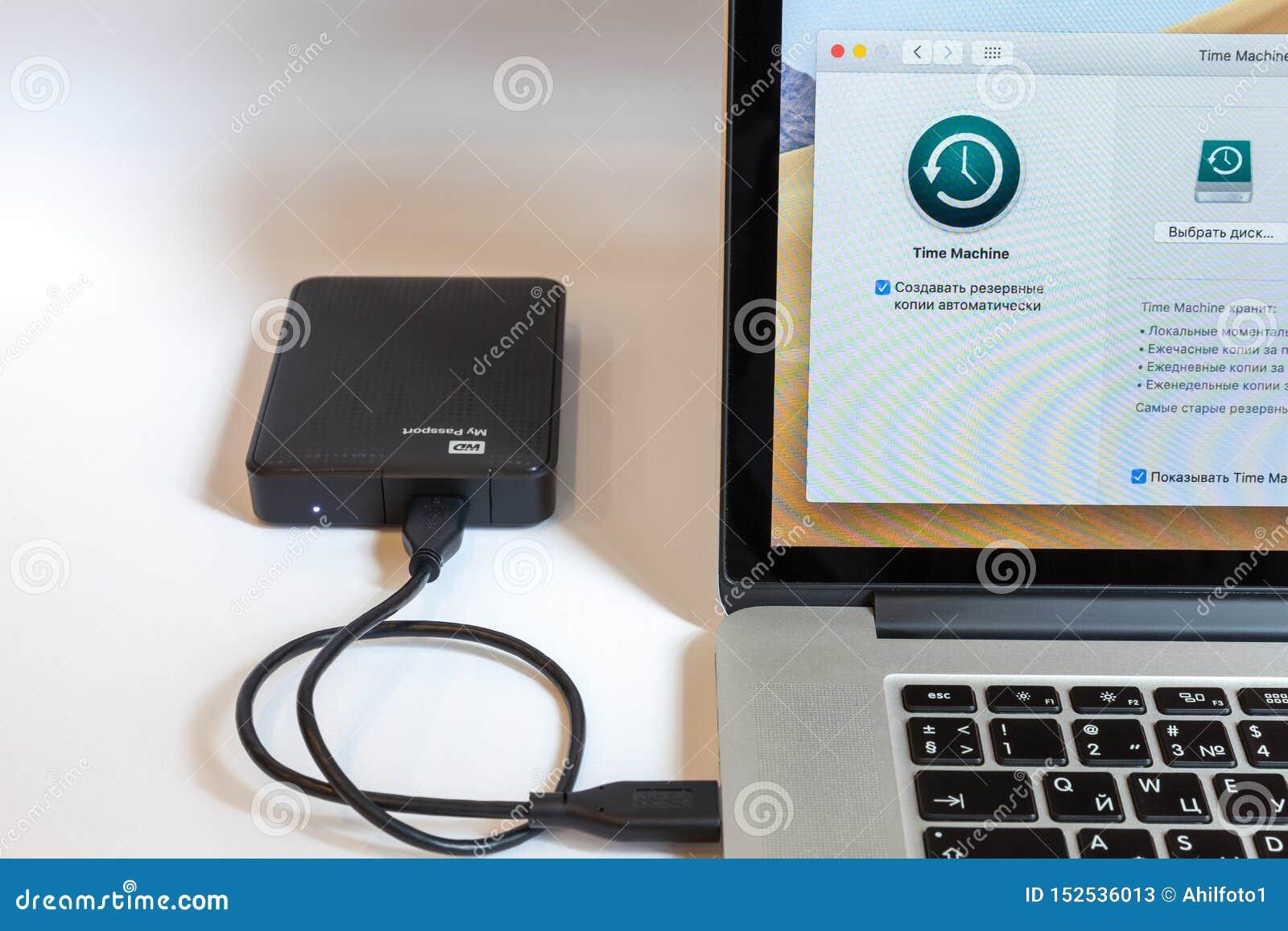莫斯科/俄罗斯- 2019年7月7日:开放MacBook,屏幕上的节目时间机器 一个外在硬盘被连接到MacBook