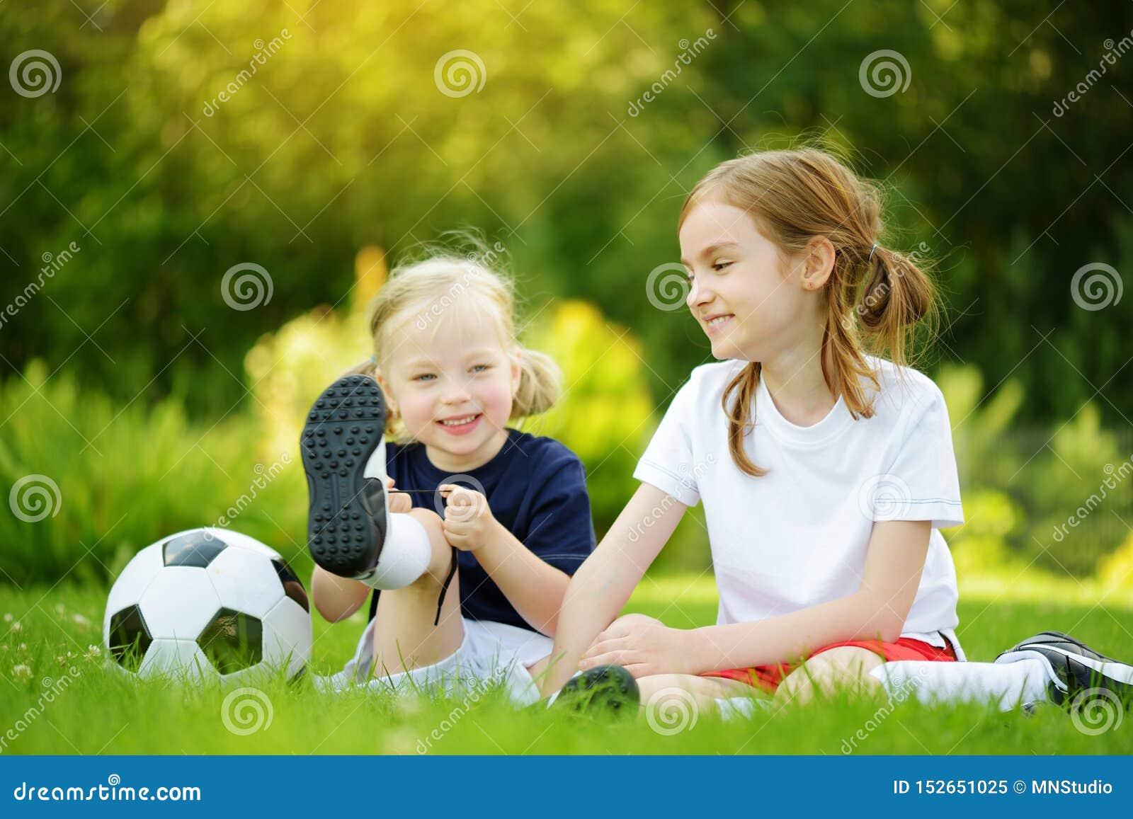 获得两个逗人喜爱的妹打一足球的乐趣在晴朗的夏日 孩子的体育活动