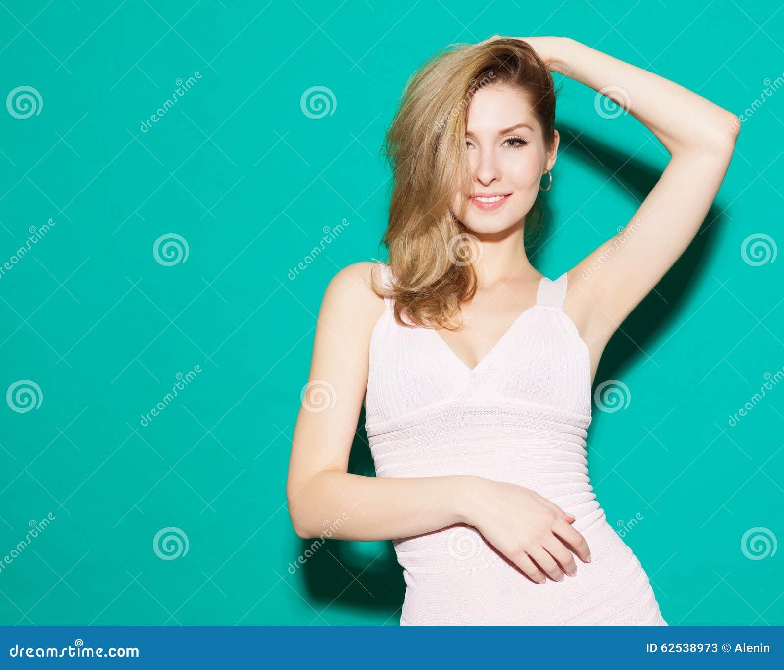 获得乐趣和愉快地摆在绿色背景的时兴的美丽的白肤金发的女孩在演播室 柔和曲调