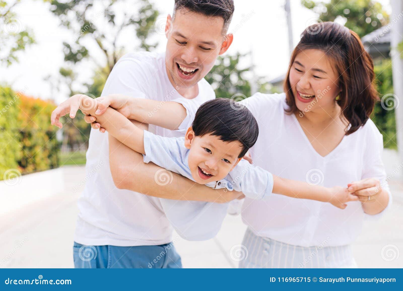获得乐趣和运载孩子的亚洲家庭在公园