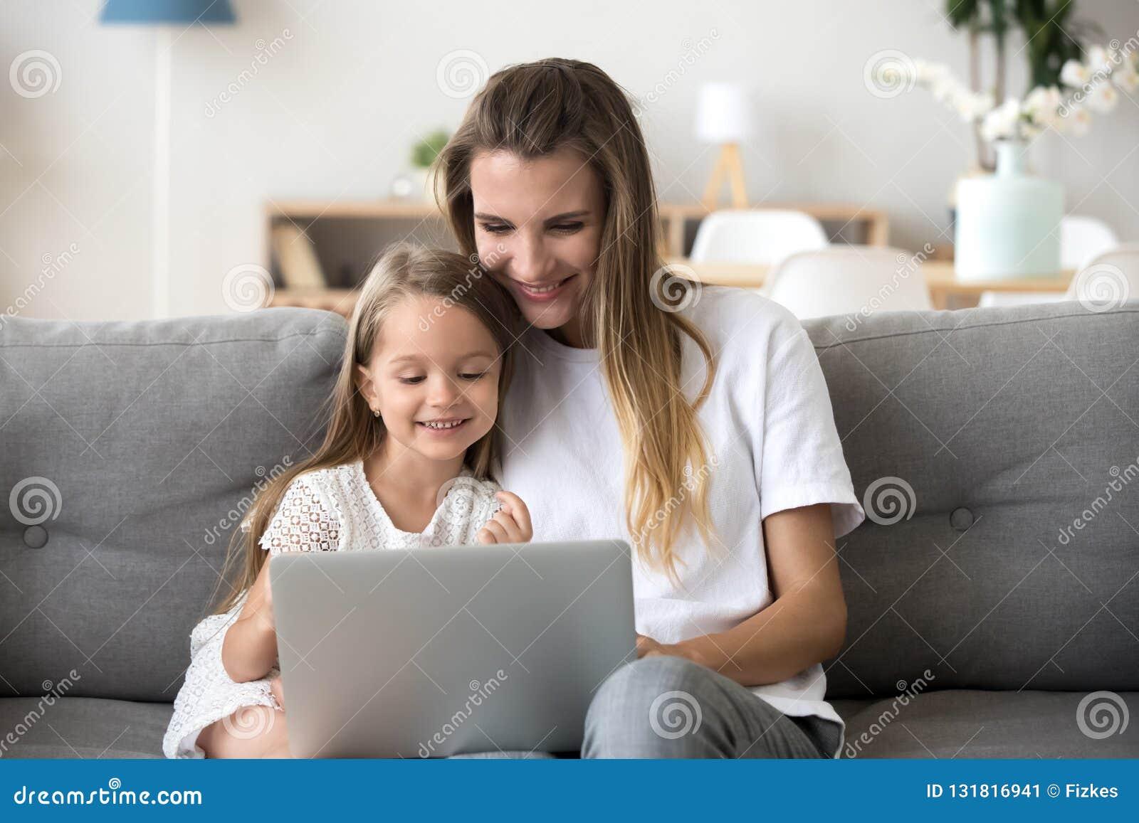 获得微笑的母亲和的孩子在网上购物与膝上型计算机的乐趣