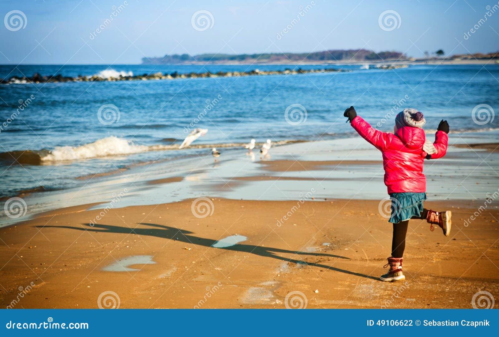 获得的女孩在冬天波罗地海滩的乐趣
