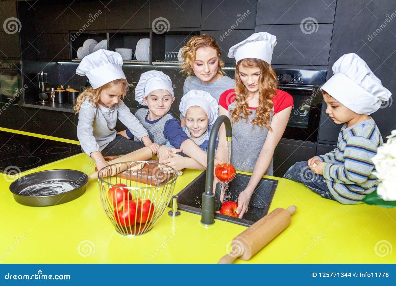获得的母亲和的孩子烹调在厨房里和乐趣