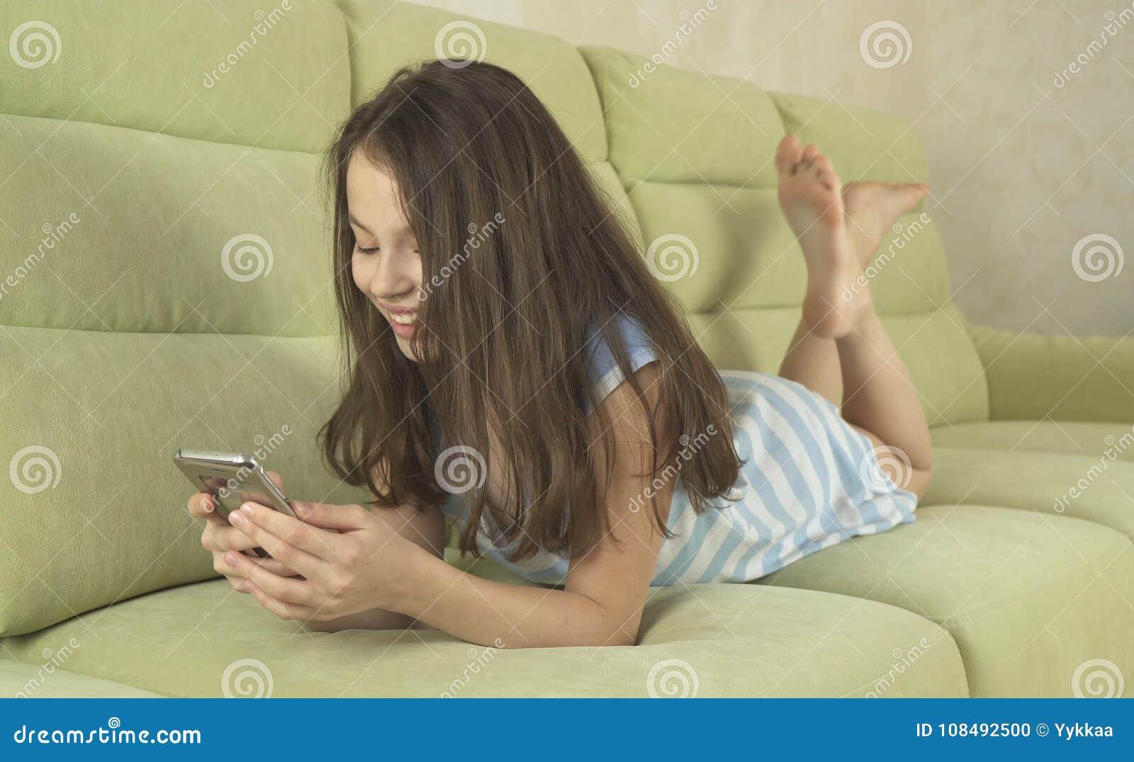 获得美丽的十几岁的女孩沟通在智能手机的乐趣
