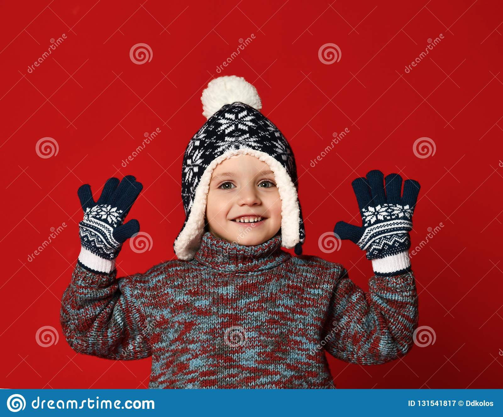 获得被编织的帽子的儿童男孩和的毛线衣和的手套在五颜六色的红色背景的乐趣