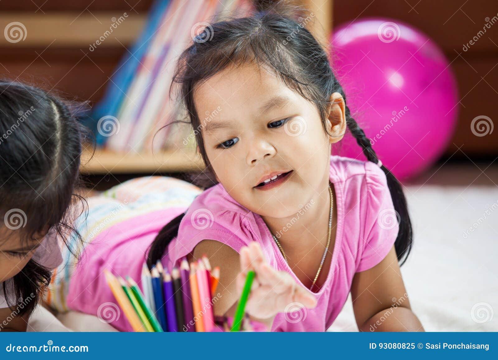 获得逗人喜爱的亚裔的小女孩乐趣绘与蜡笔