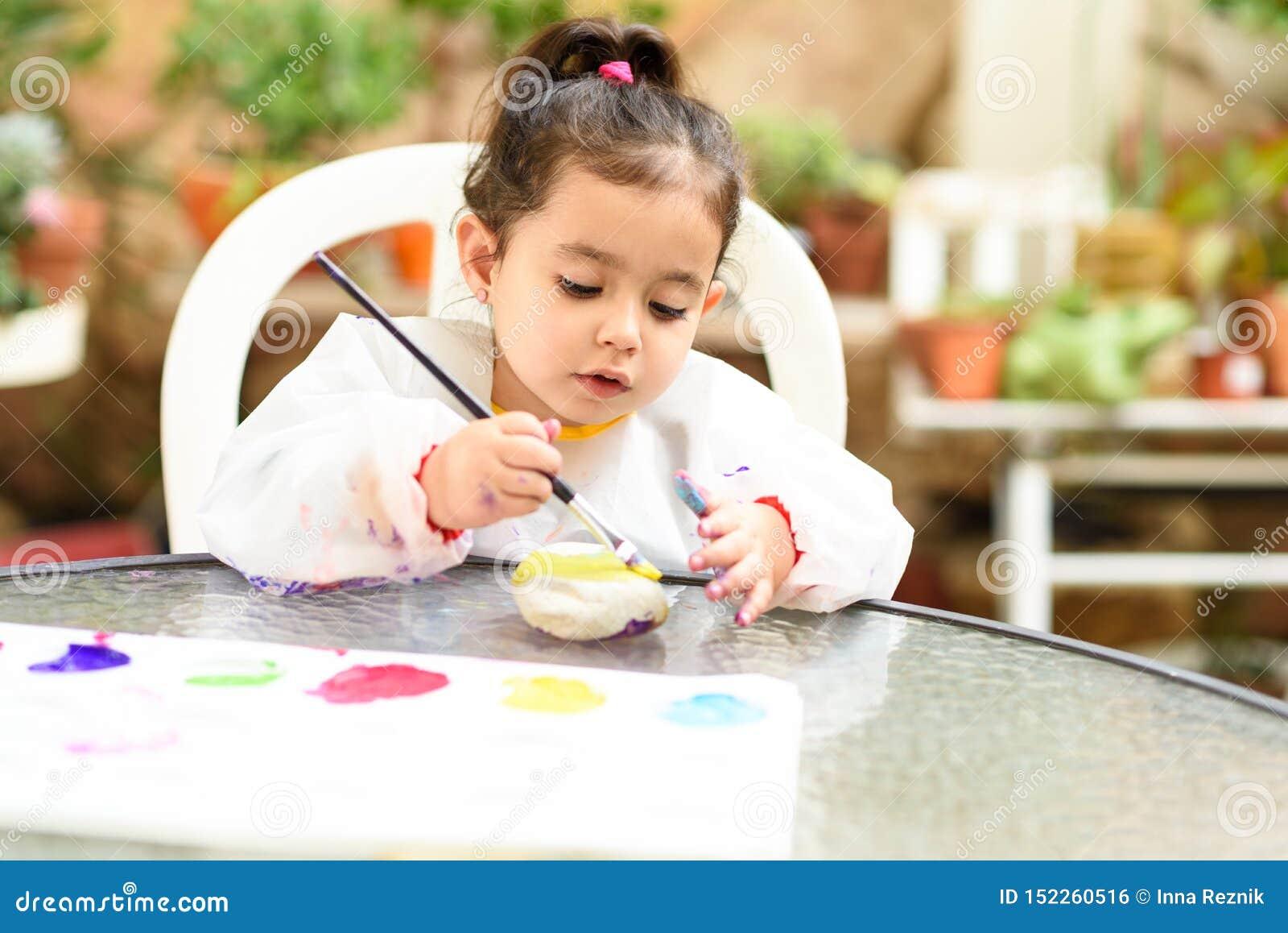 获得逗人喜爱的女孩乐趣,上色与刷子,使用和绘 有油漆的学龄前儿童在庭院