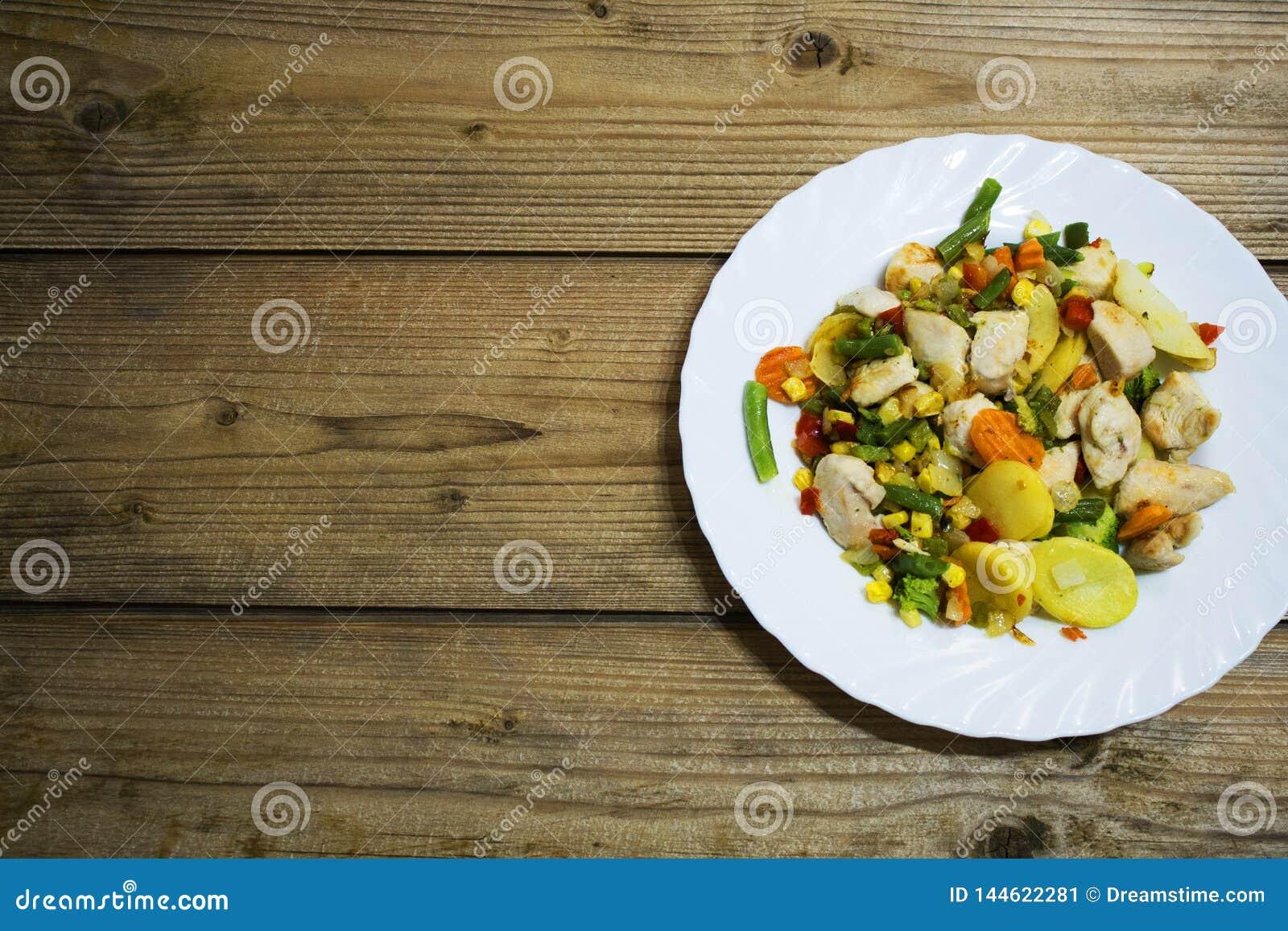 菜和鸡胸脯在木桌上