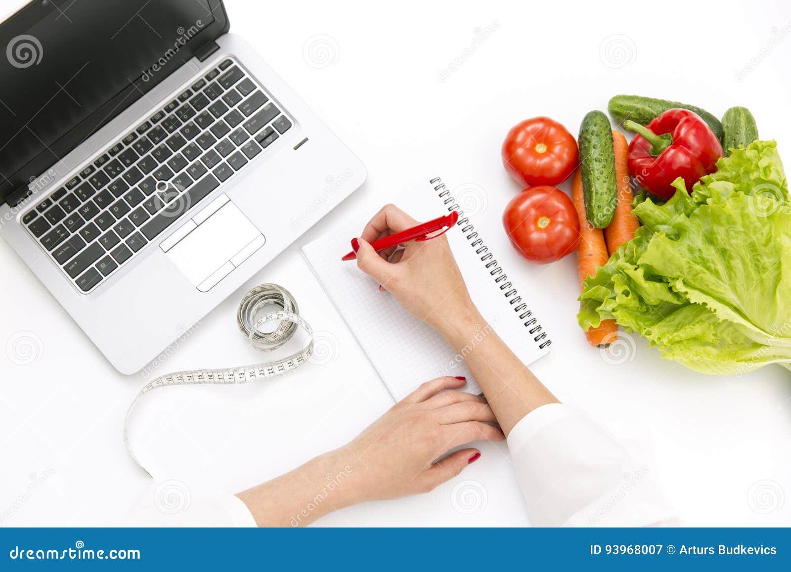 菜饮食营养或药剂概念 写饮食的医生手计划,成熟菜构成,膝上型计算机和测量