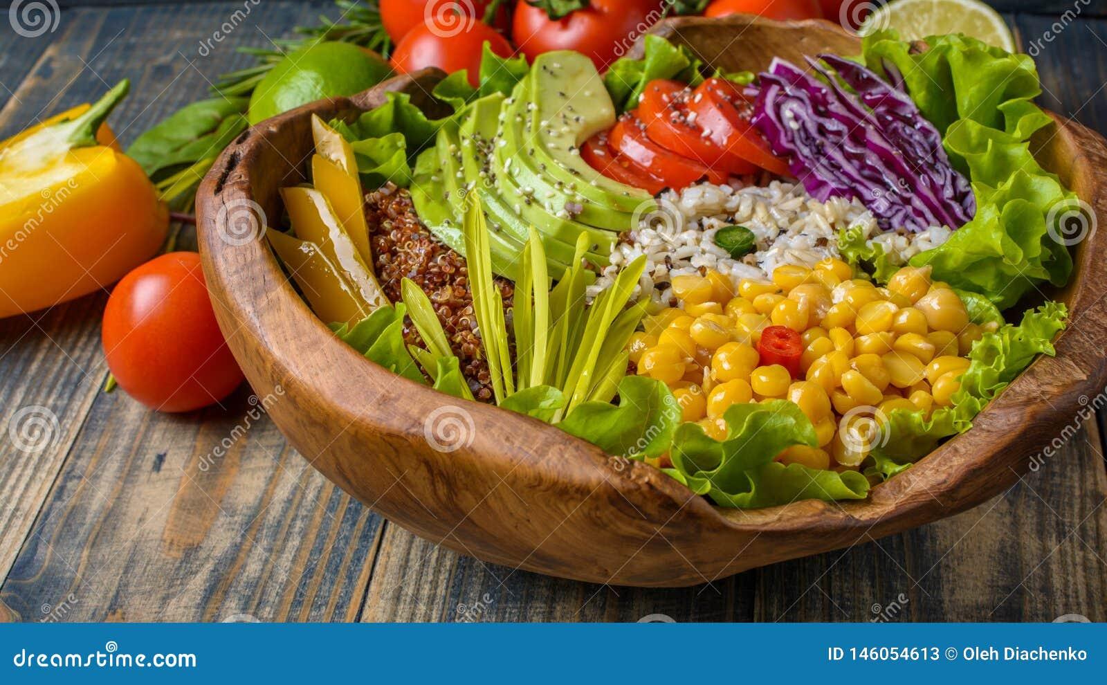 菩萨碗用鸡豆,鲕梨,水菰,奎奴亚藜种子,甜椒,蕃茄,绿色,圆白菜,在老破旧木的莴苣