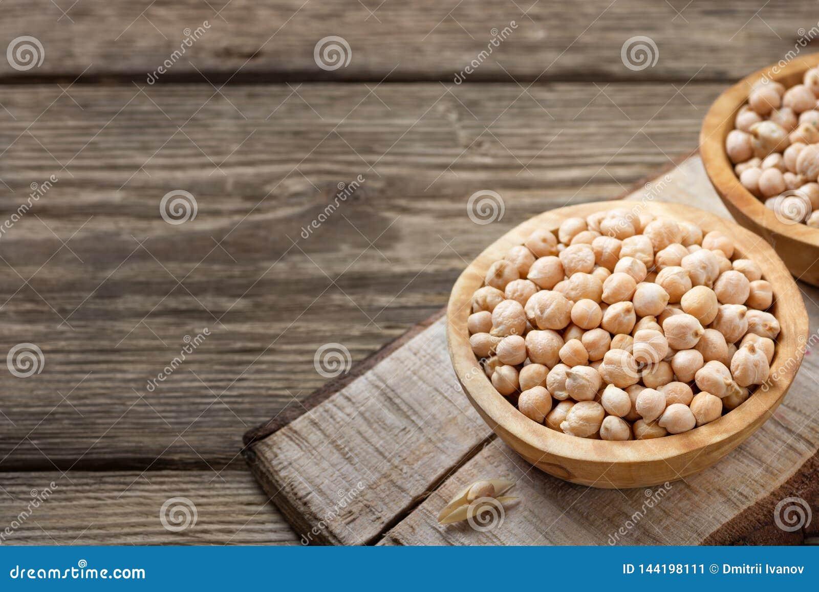 营养素密集的食物-在碗的未加工的鸡豆五谷在一张木土气桌上