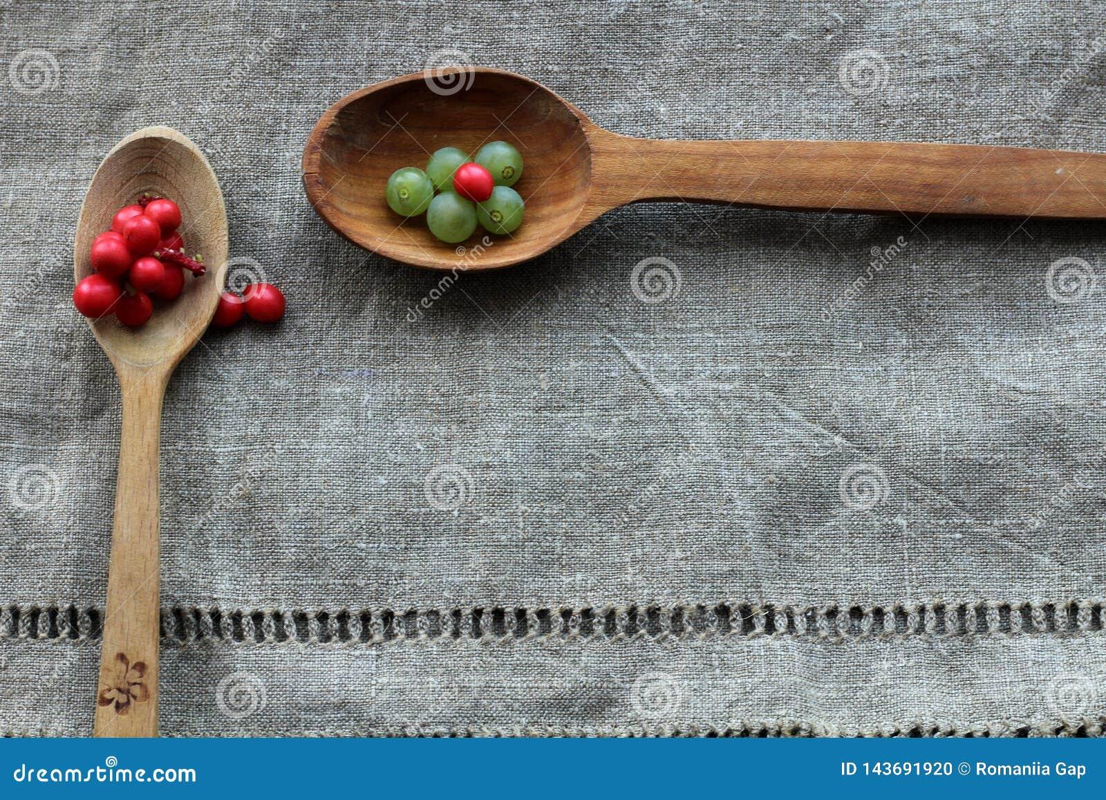 葡萄小绿色莓果和柠檬香茅红色莓果在说谎在布料的两把木匙子的由麻袋布制成