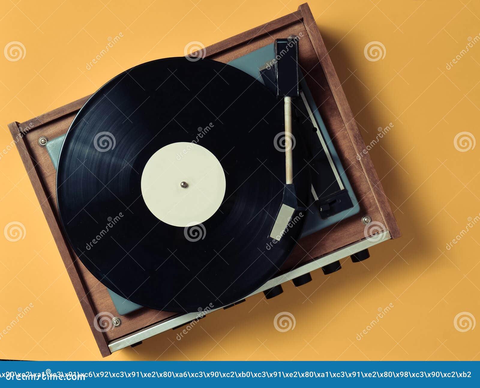 葡萄酒与乙烯基板材的乙烯基转盘在黄色淡色背景 听音乐 顶视图