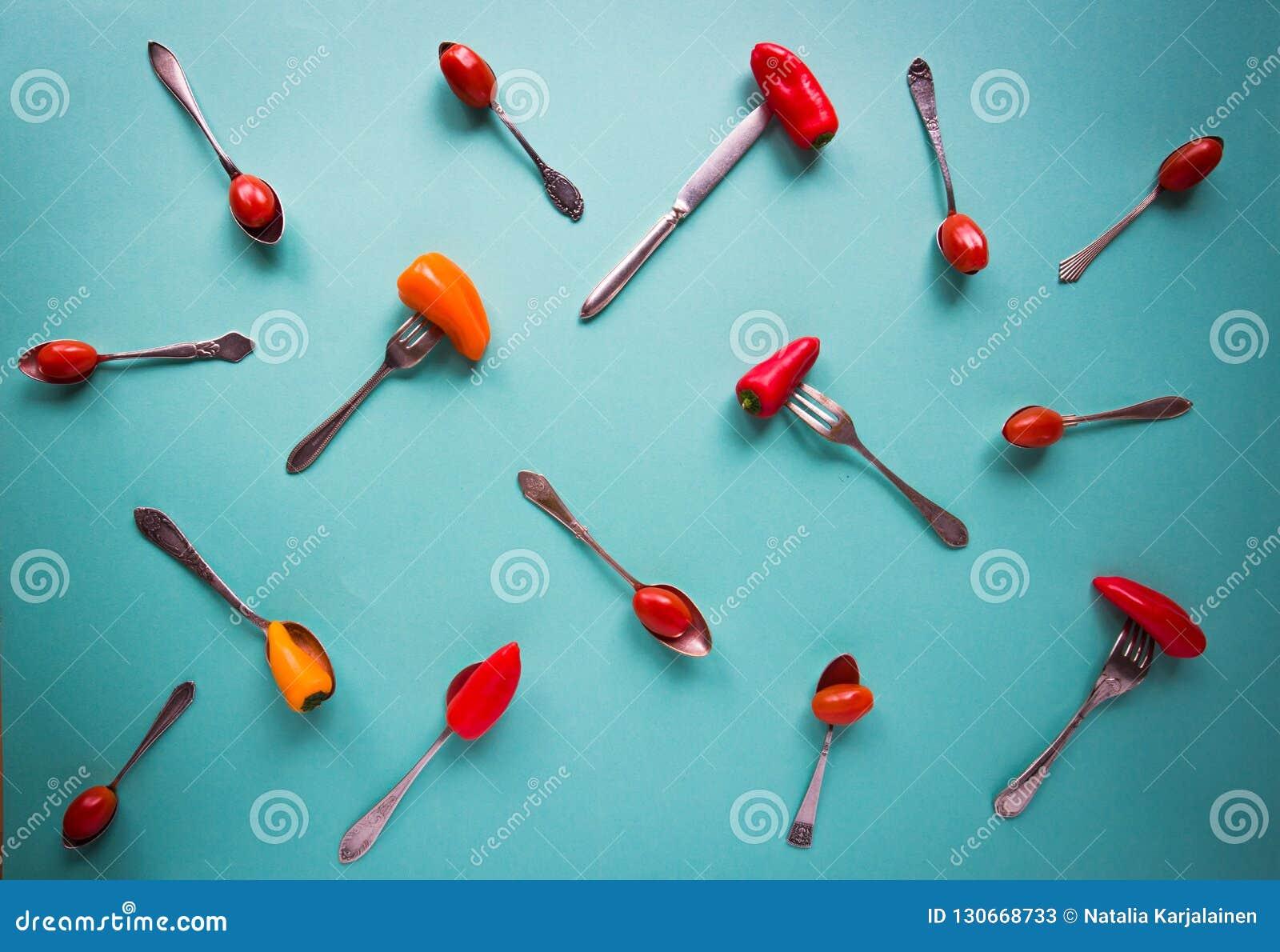 葡萄酒匙子、叉子和刀子用辣椒粉和西红柿在蓝色背景