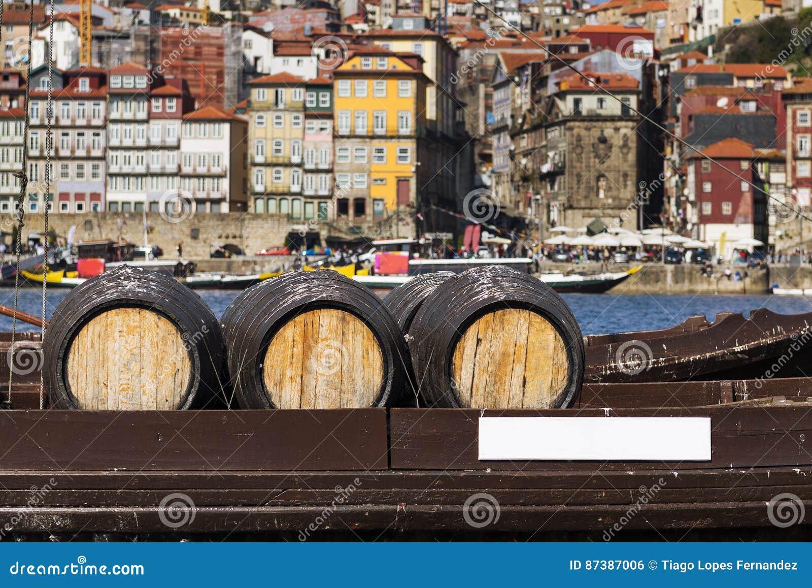 葡萄酒在一条小船在背景中滚磨在有市的杜罗河河波尔图