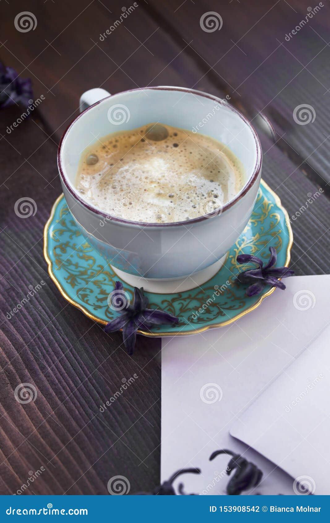 葡萄酒杯子与淡紫色花的og咖啡