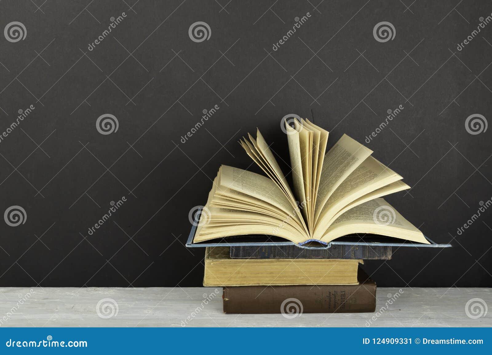 葡萄酒老精装书书,在红色背景的被扇动的页 回到学校 复制空间 教育背景