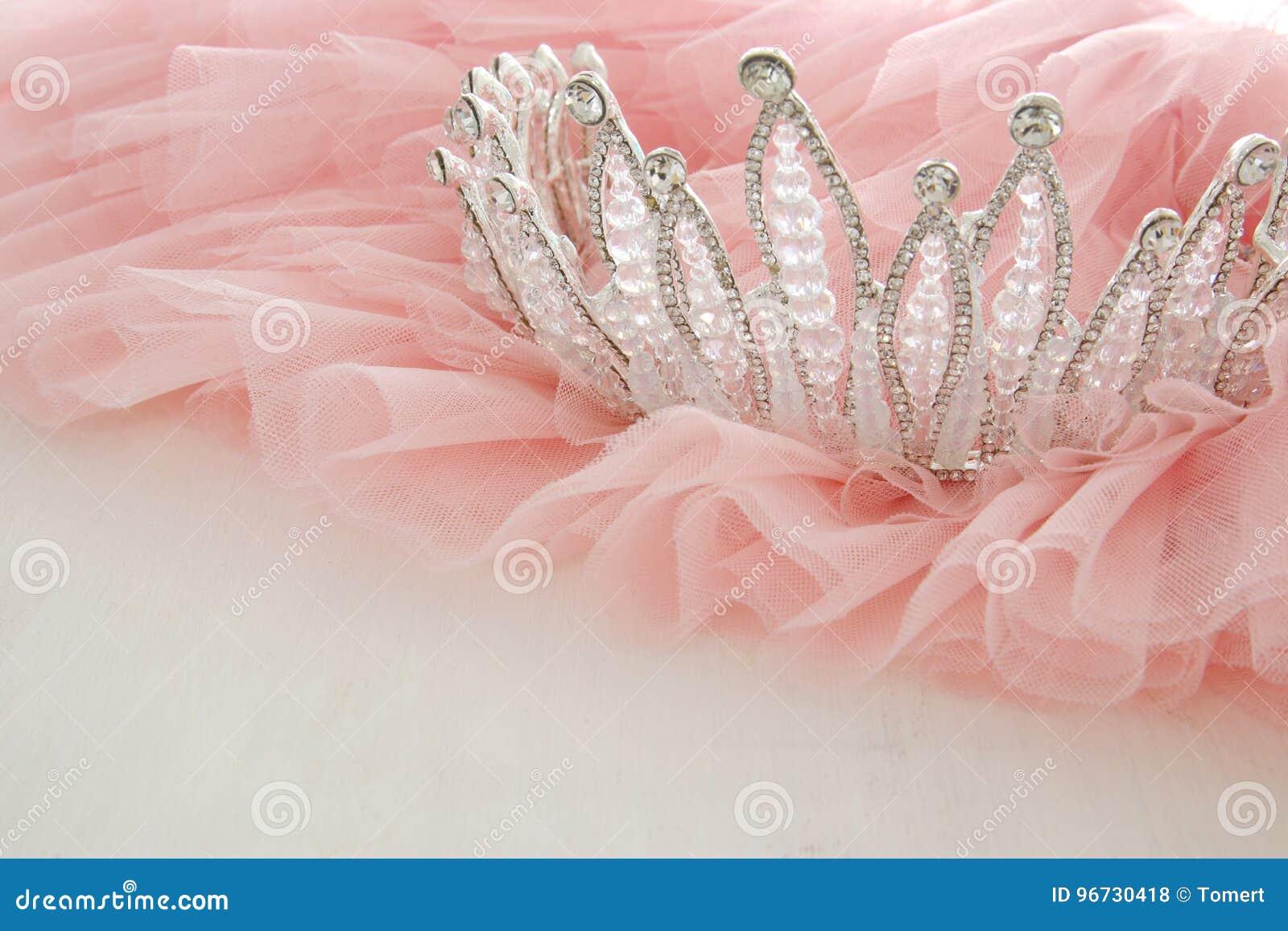 葡萄酒薄纱桃红色薄绸的礼服和金刚石冠状头饰在木白色桌上 婚礼和girl& x27; s党概念