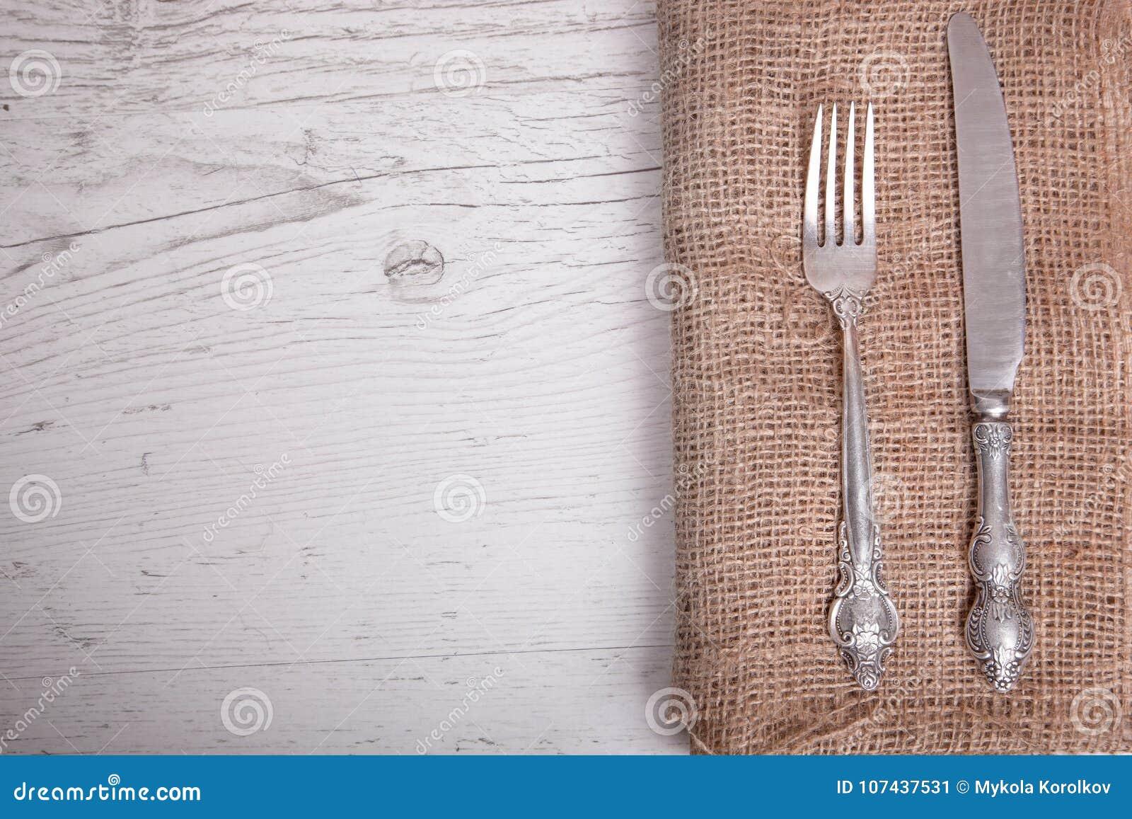 葡萄酒银色碗筷刀子和叉子在餐巾,在老