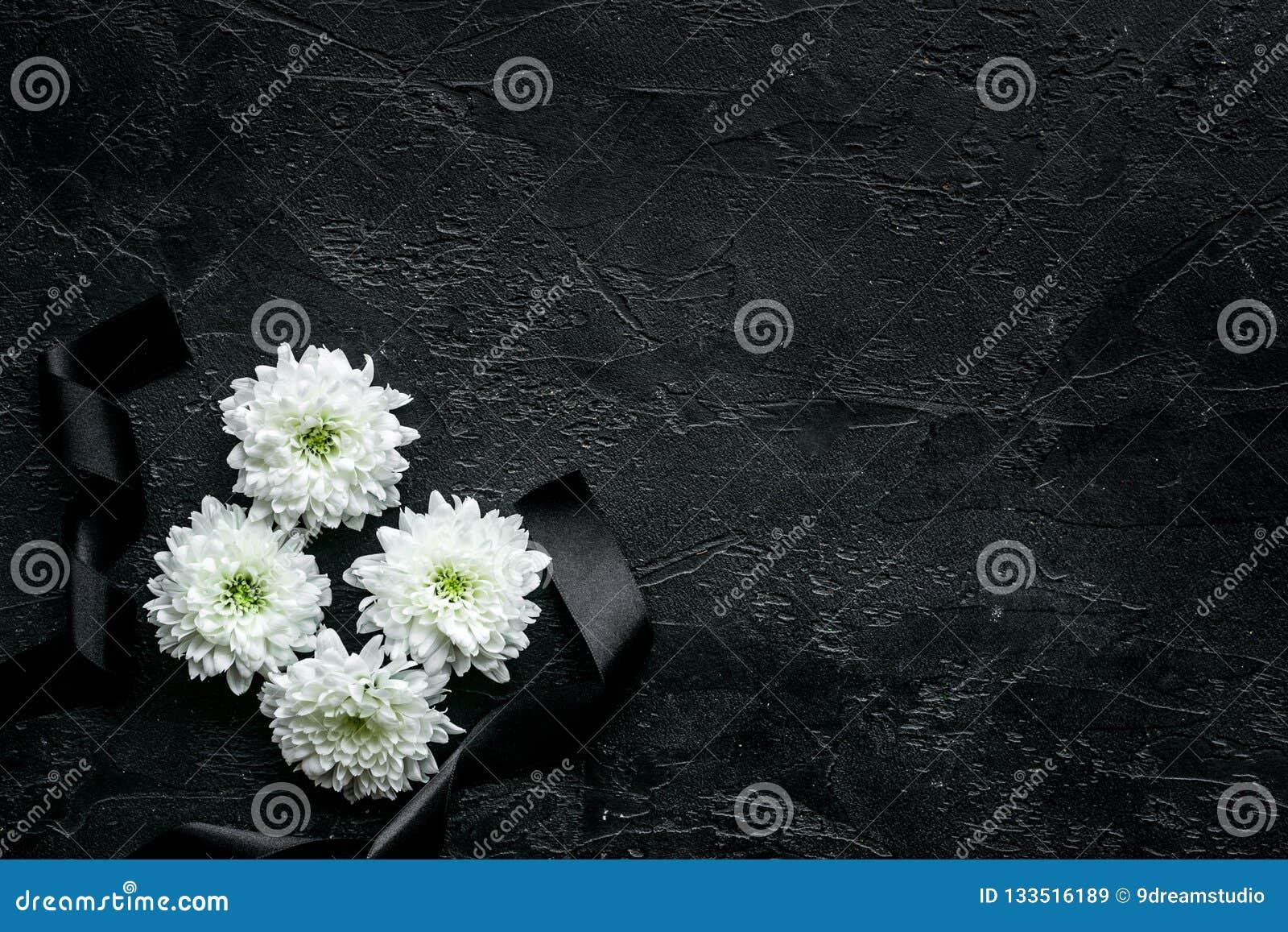 葬礼标志 在黑丝带附近的白花在黑背景顶视图拷贝空间