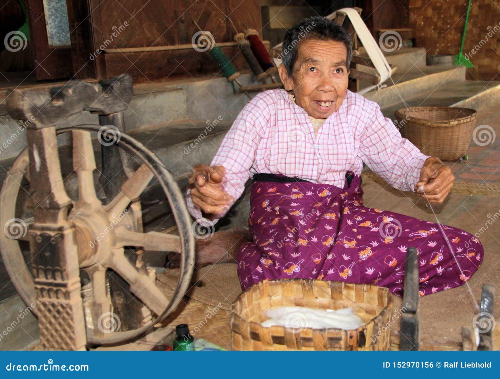 蒲甘,缅甸- 12月21 2015年:转动在与古老木轮子的一个简单的小屋前面的老缅甸人