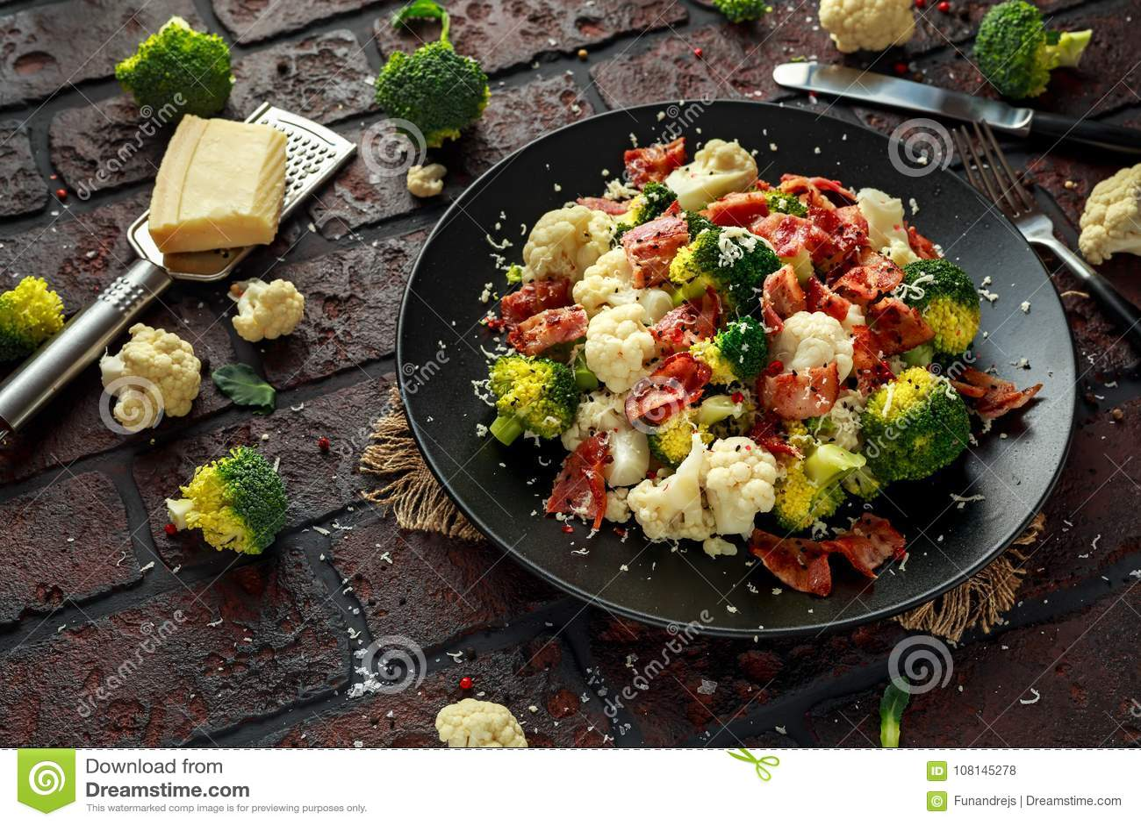 蒸的硬花甘蓝,花椰菜沙拉用烟肉,在一个黑色的盘子的帕尔马干酪 健康概念的食物