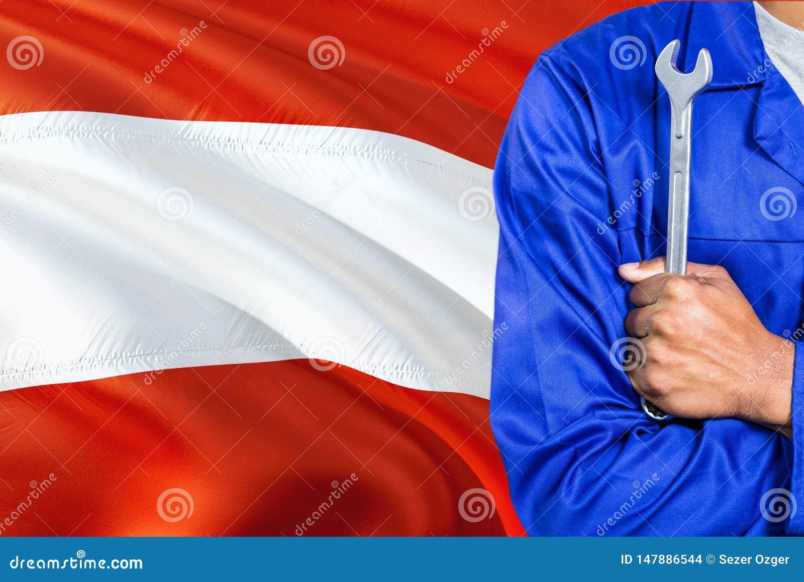 蓝色制服的奥地利技工拿着板钳反对挥动奥地利旗子背景 横渡的胳膊技术员