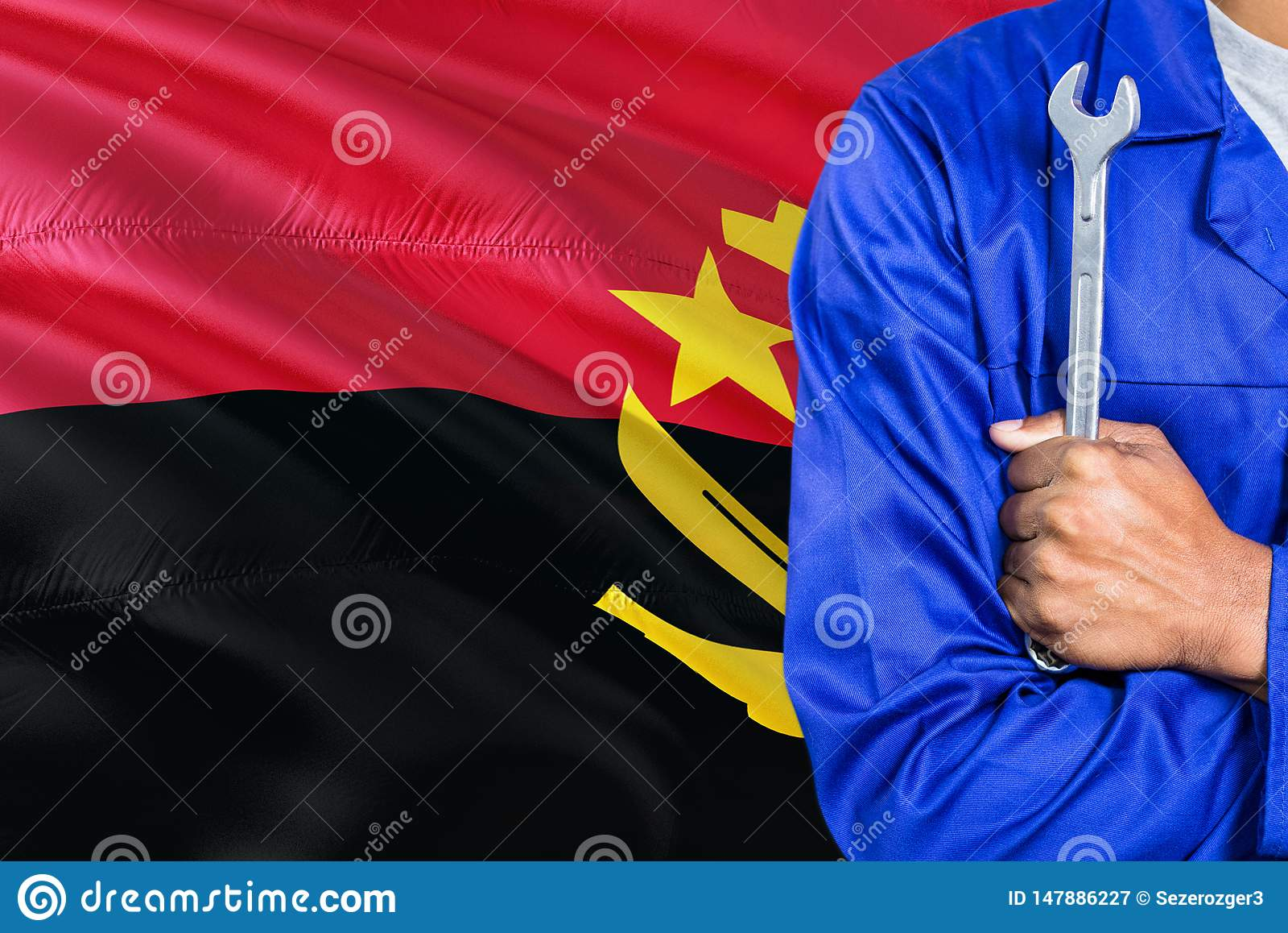 蓝色制服的安哥拉技工拿着板钳反对挥动安哥拉旗子背景 横渡的胳膊技术员