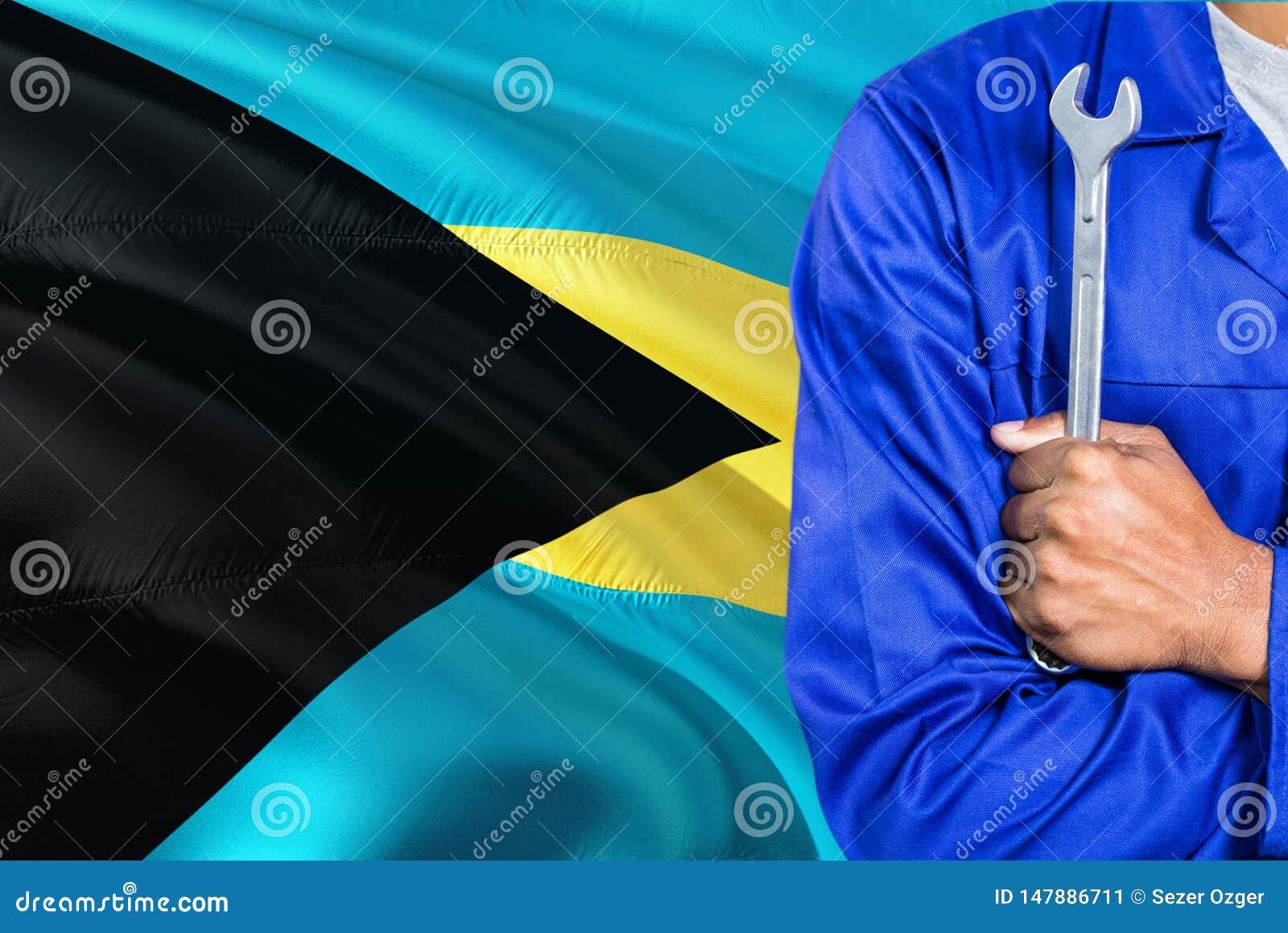 蓝色制服的巴哈马群岛的技工拿着板钳反对挥动巴哈马旗子背景 横渡的胳膊技术员