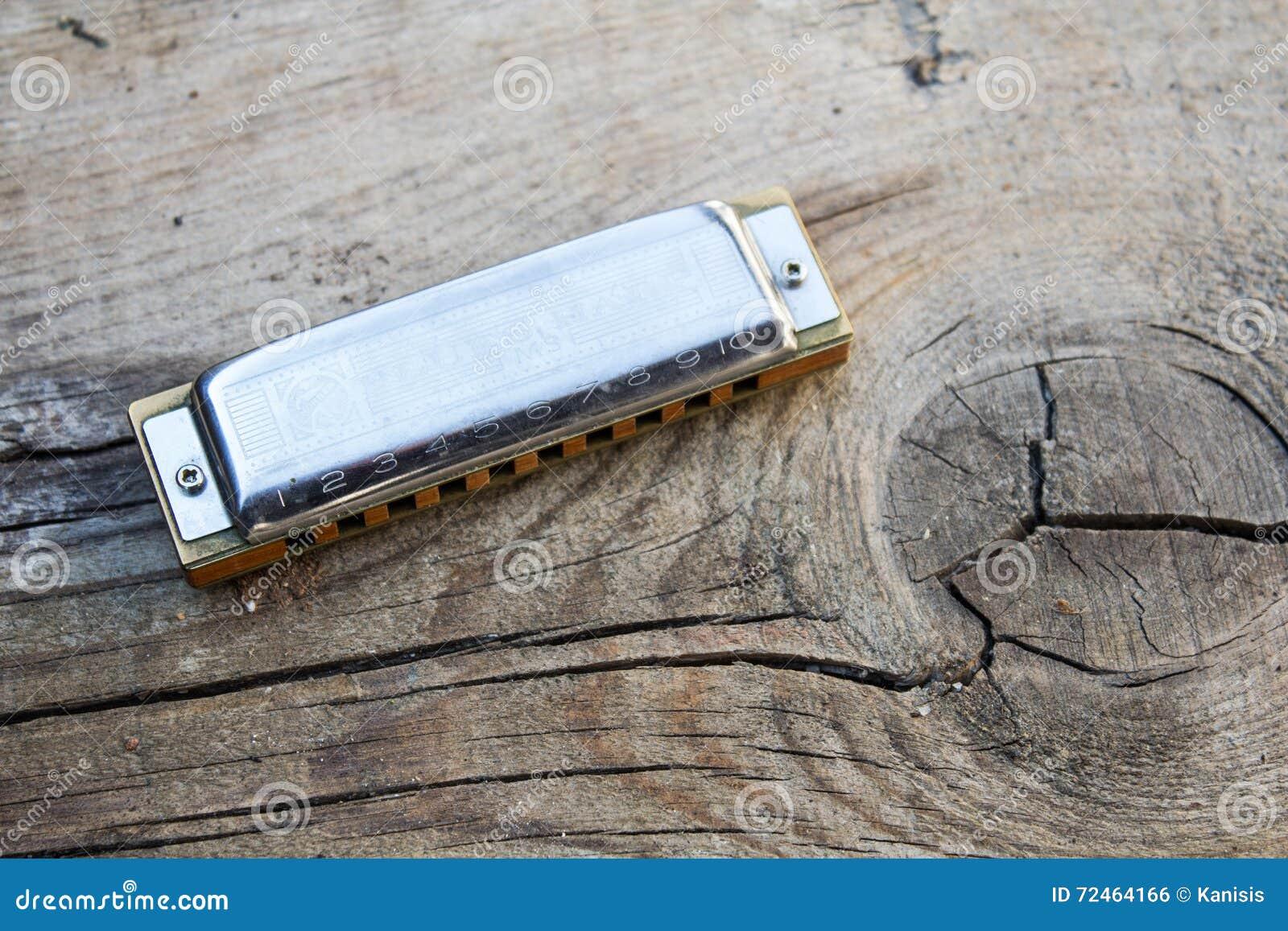 蓝色口琴在老木背景的乐器