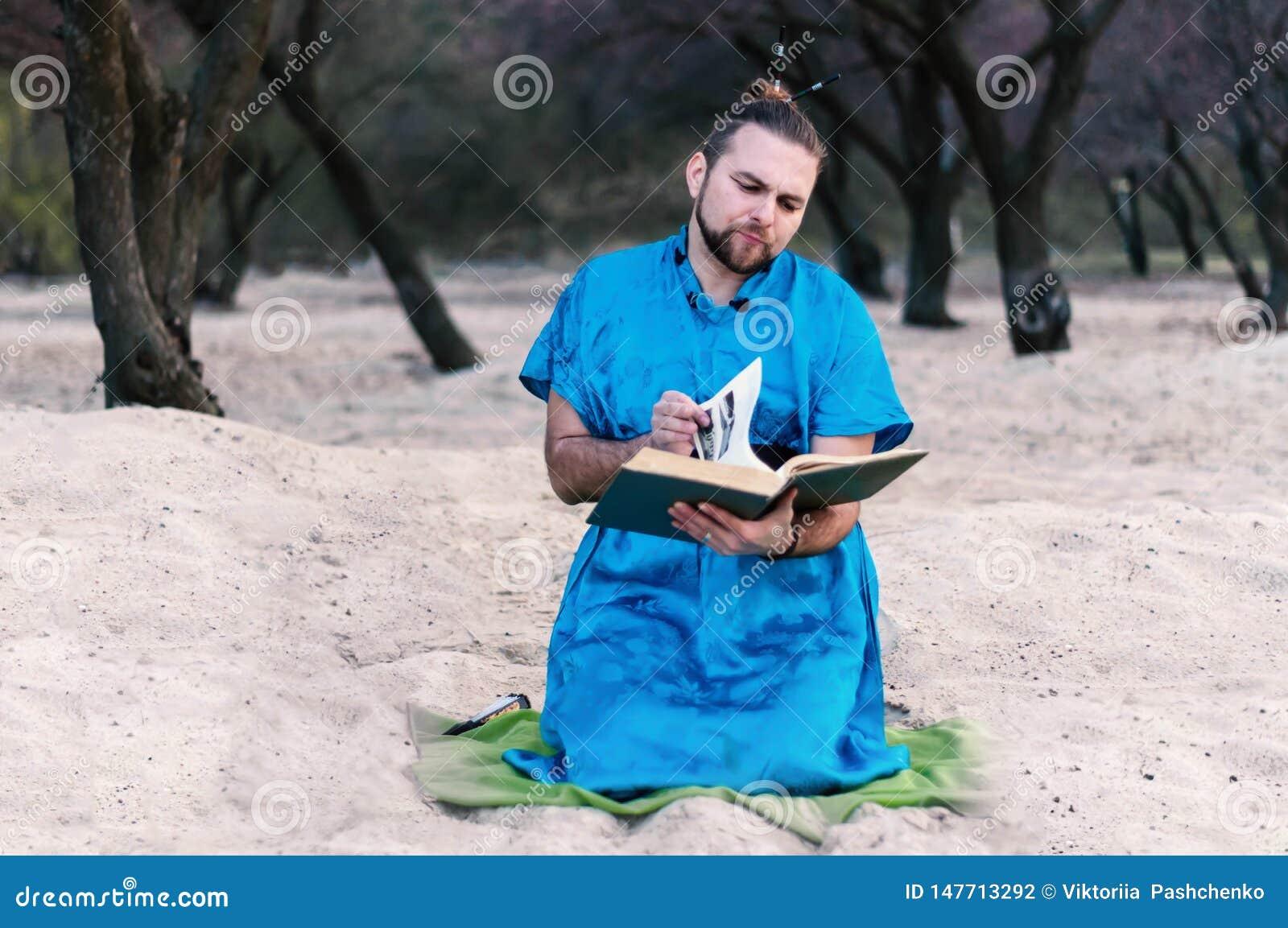 蓝色和服开会的严肃的英俊的有胡子的人,生叶通过大书