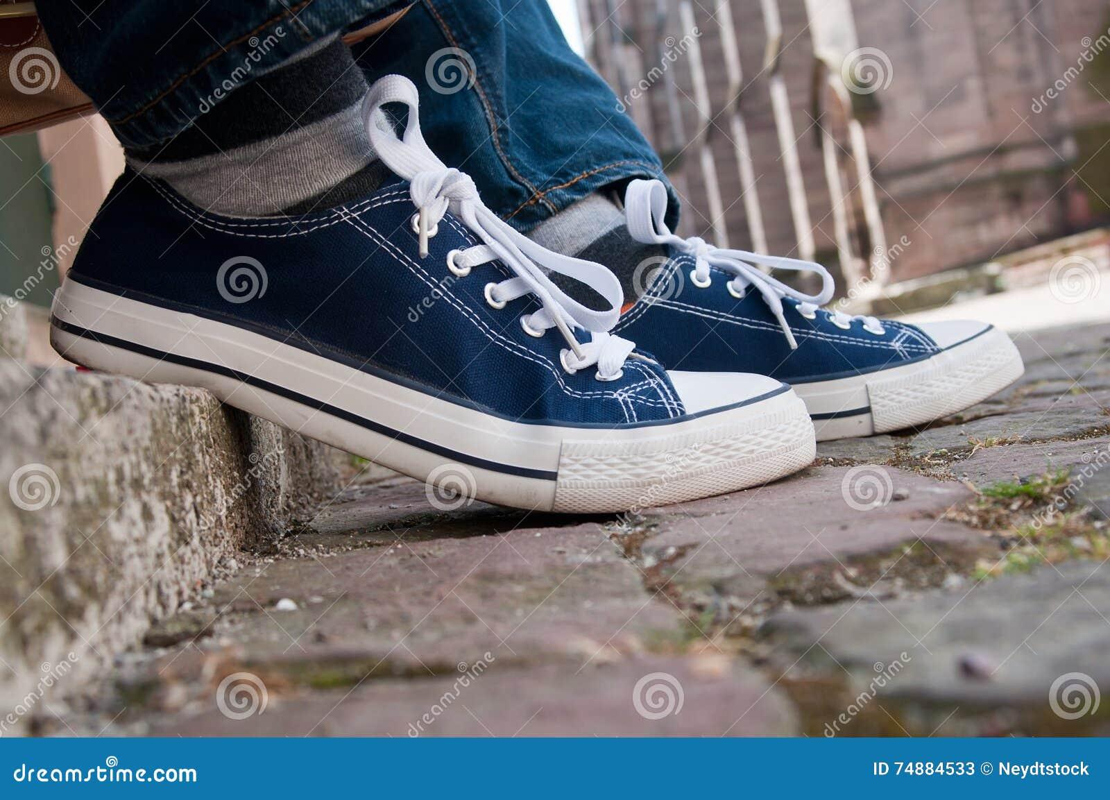 蓝色夏天运动鞋和蓝色牛仔裤在室外