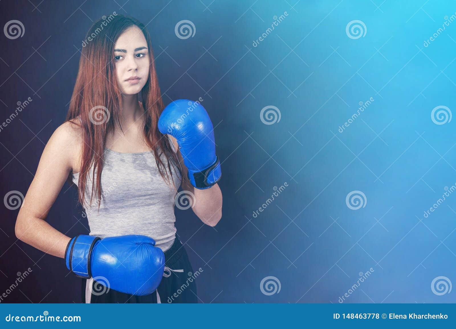 蓝色拳击手套的拳击手女孩在机架的一件灰色T恤杉在灰色背景